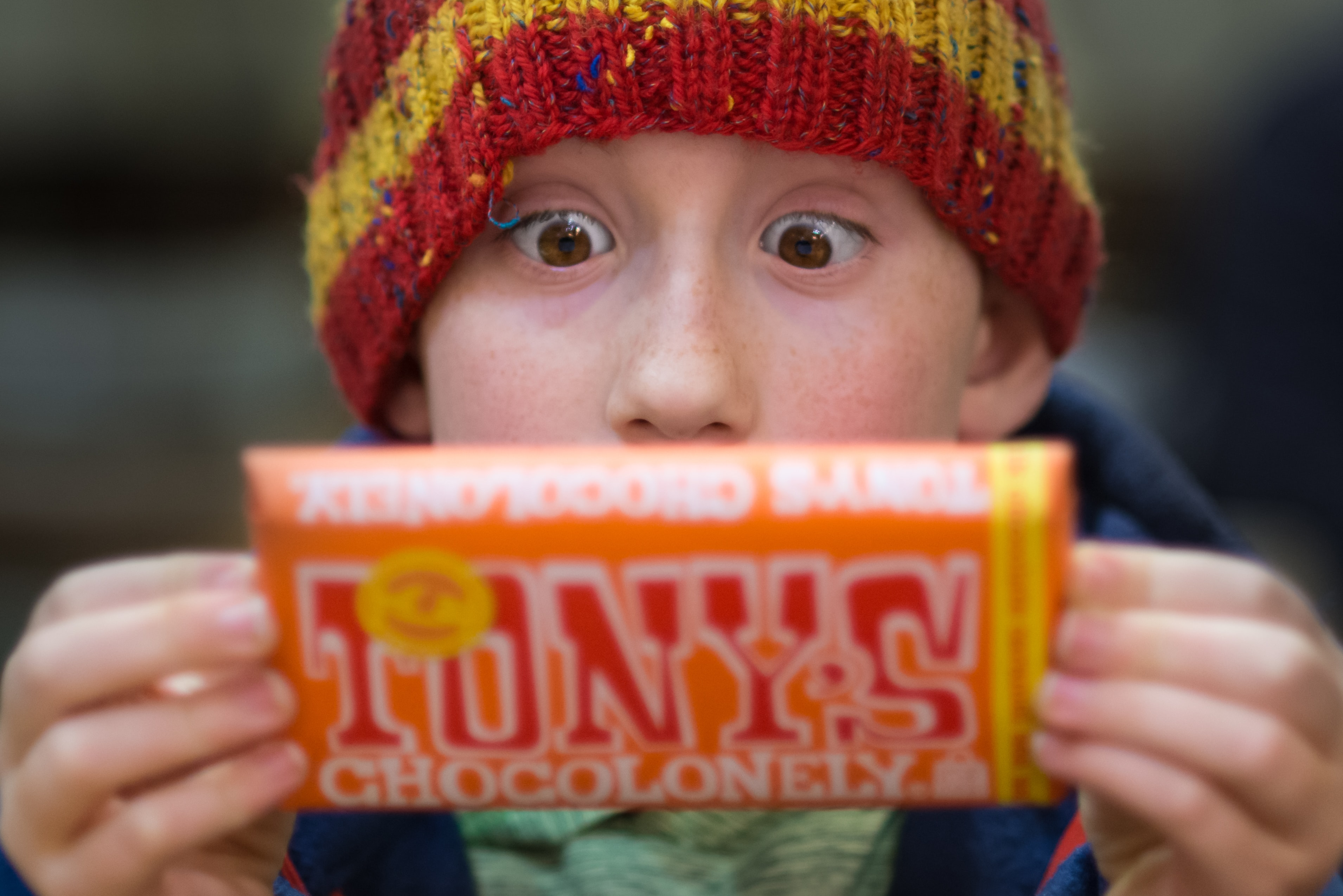 A little boy wearing a striped beanie reading the label of a chocolate bar in Portland