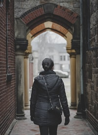 person standing on alleyway during daytime