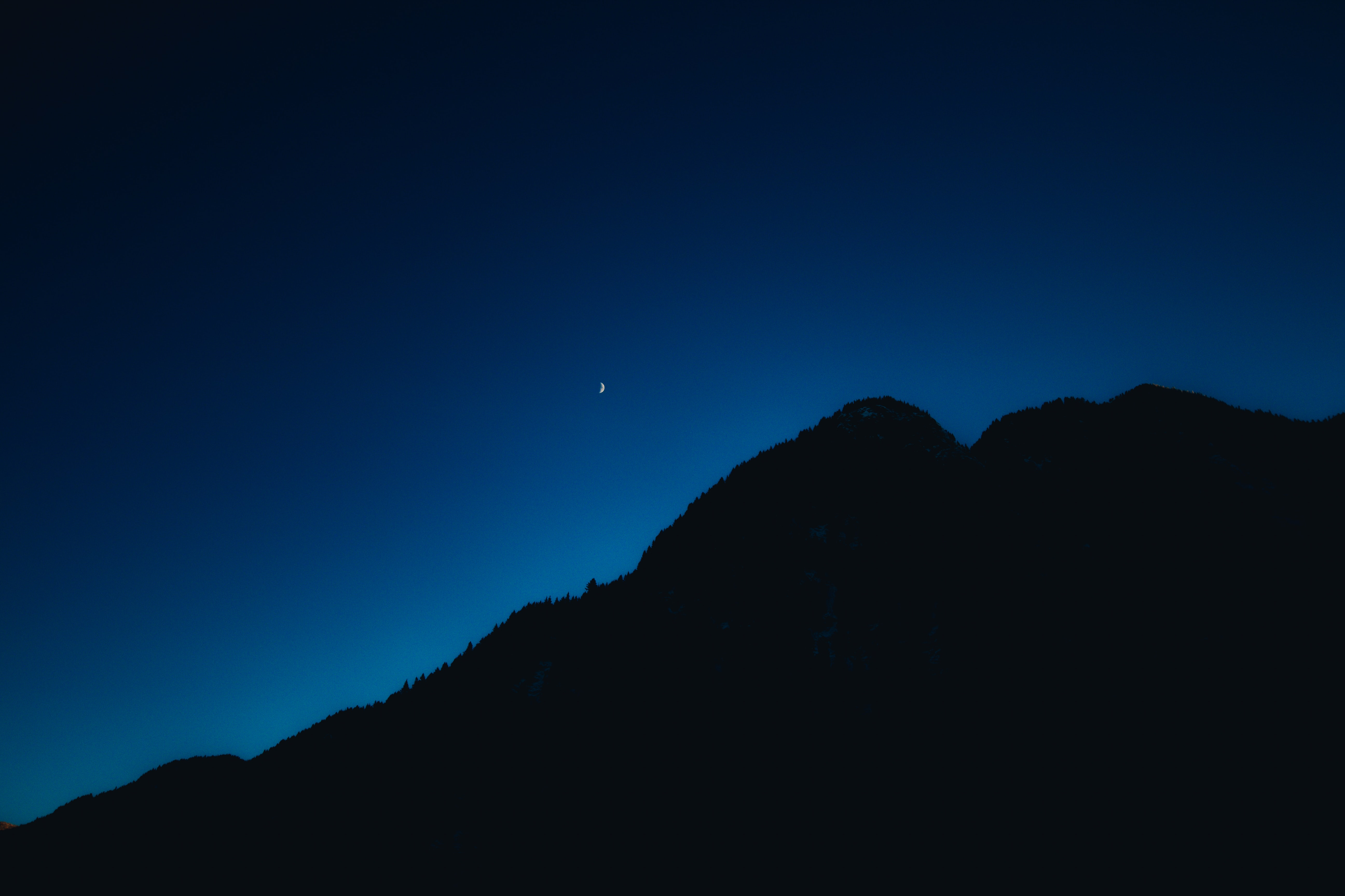 A silhouette of a wooded mountain under an evening sky with a crescent moon