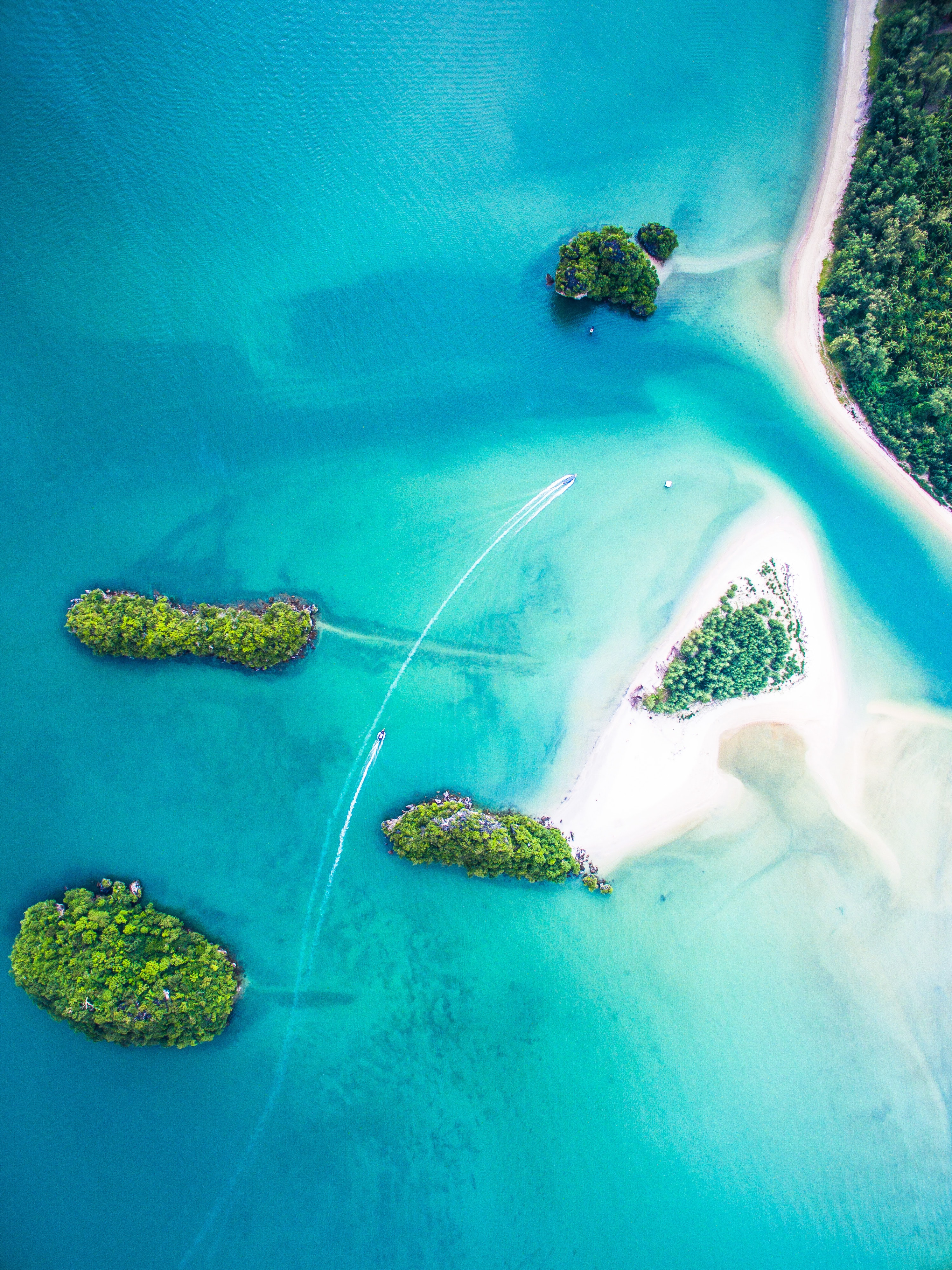 An aerial shot of two motorboats speeding on clear water between small tropical islands