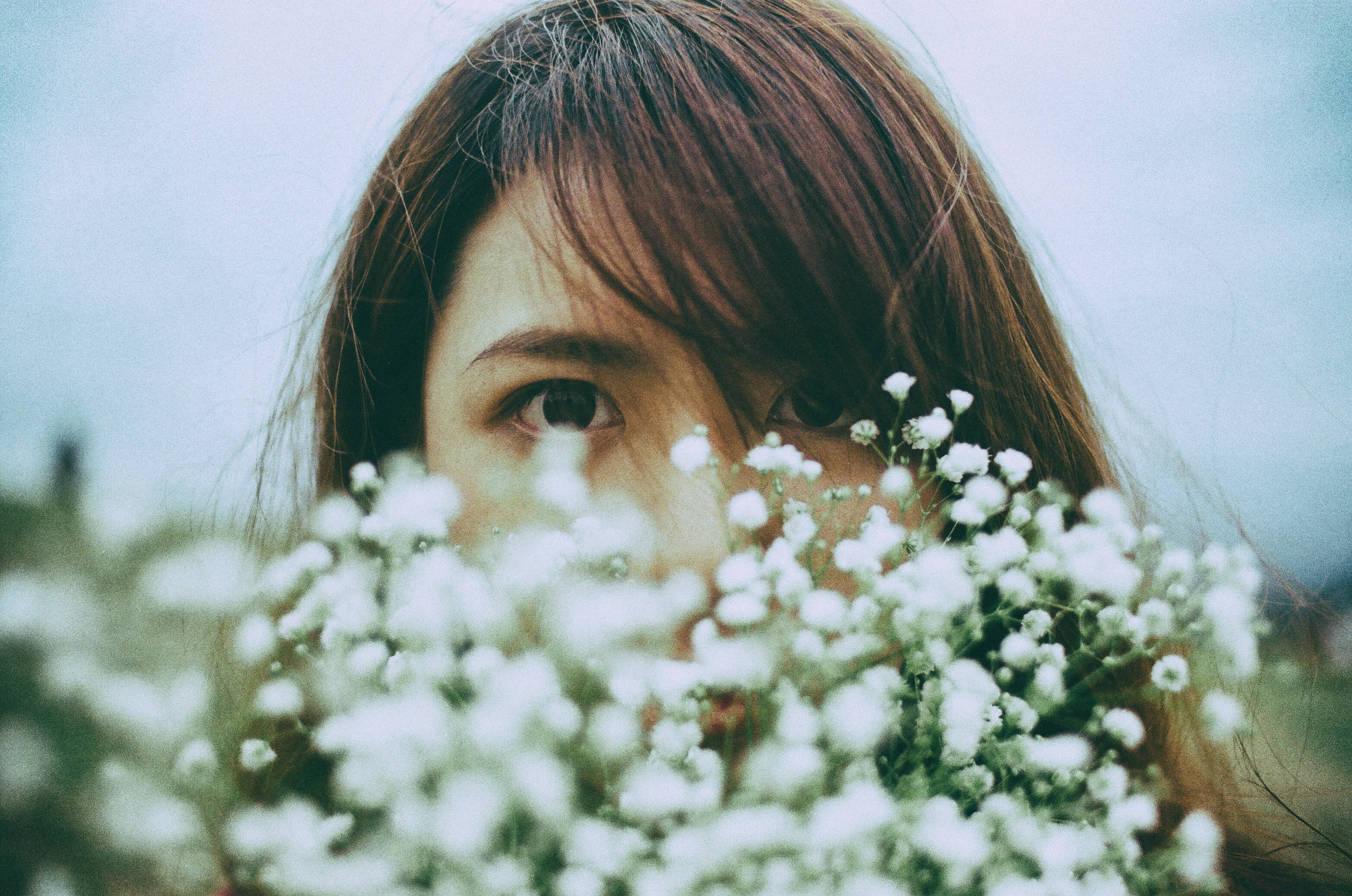 A dark-haired woman's face behind a bunch of tiny white flowers