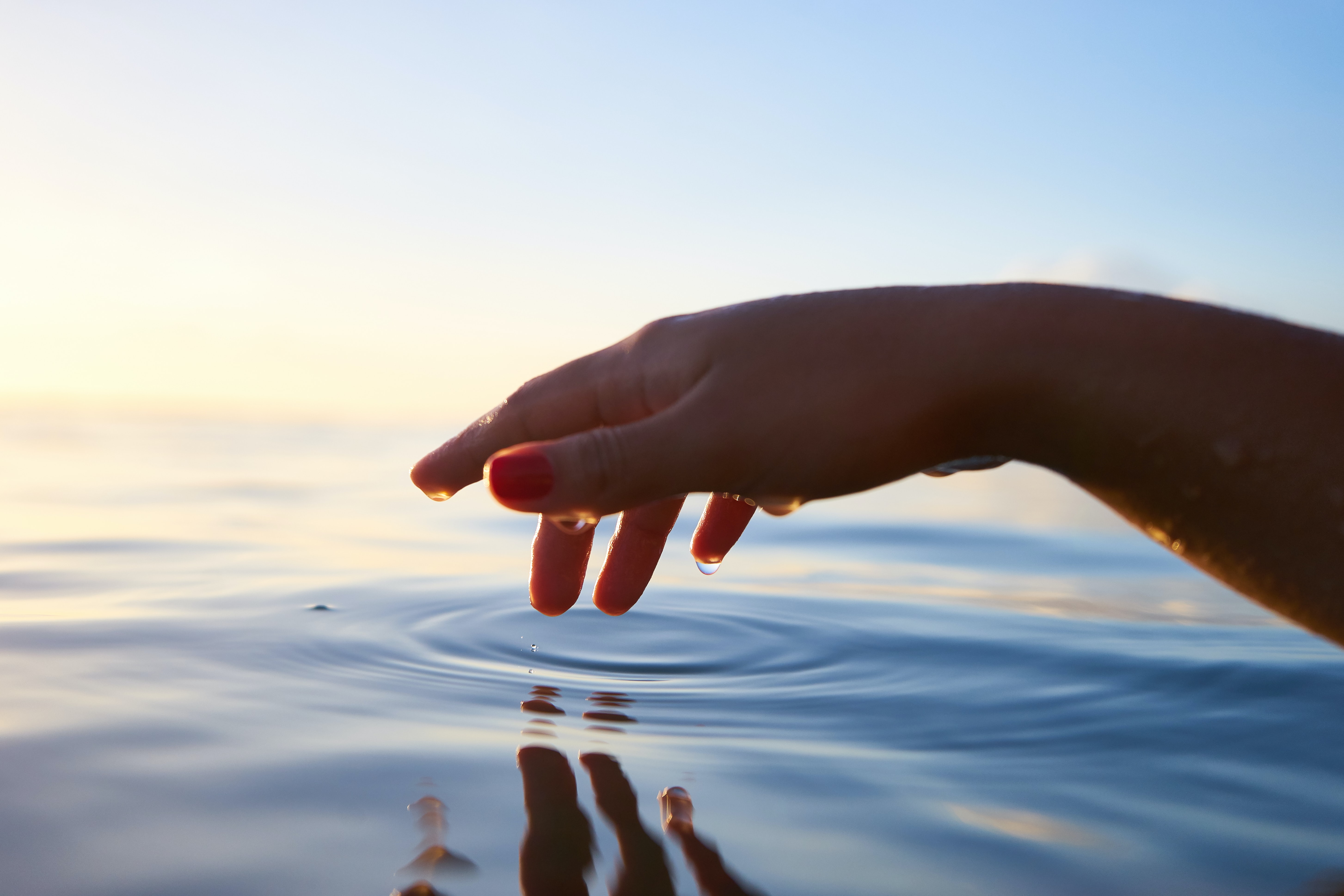 person about to touch the calm water