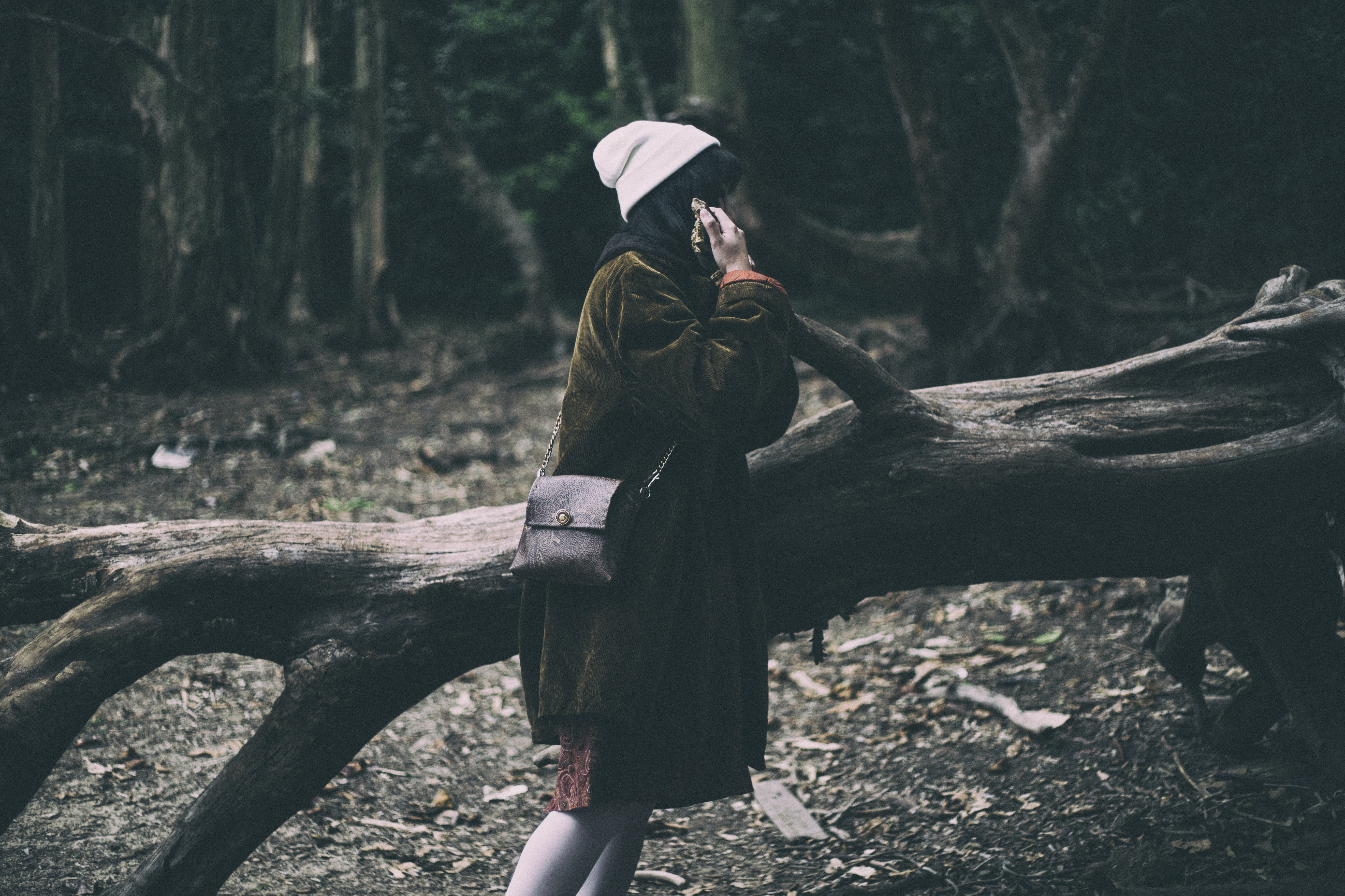 Woman wearing layers of coats talking on the phone in the woods