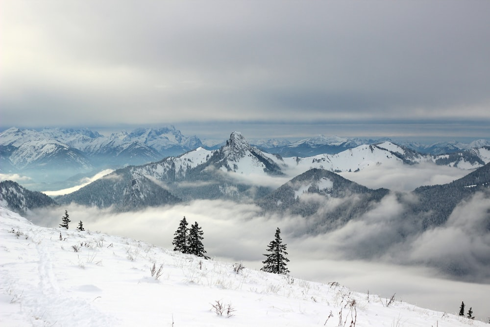 snow covered mountains under grey clouds