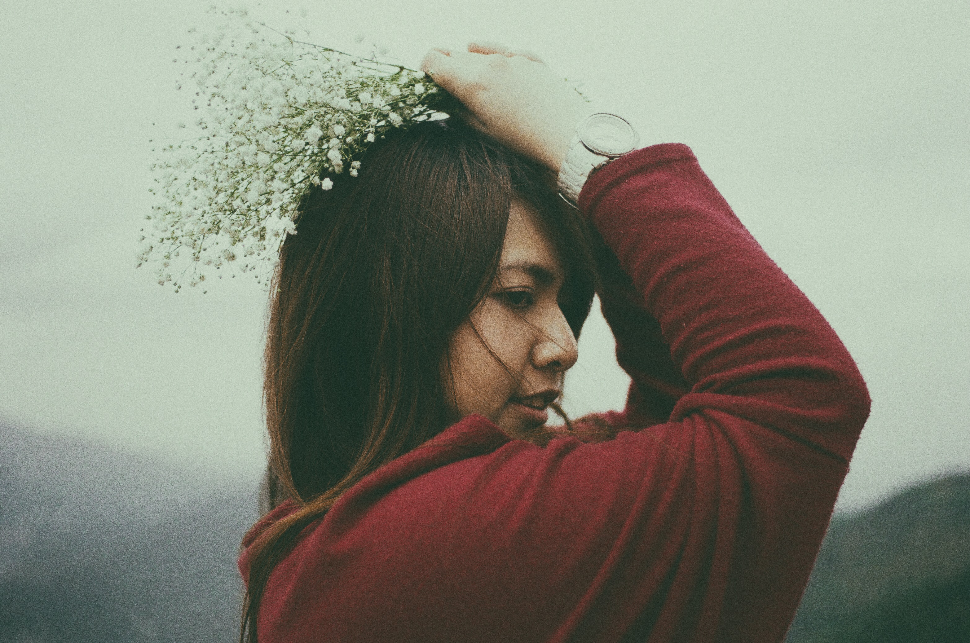 A dark-haired woman holding a bouquet of baby's-breath flowers over her head