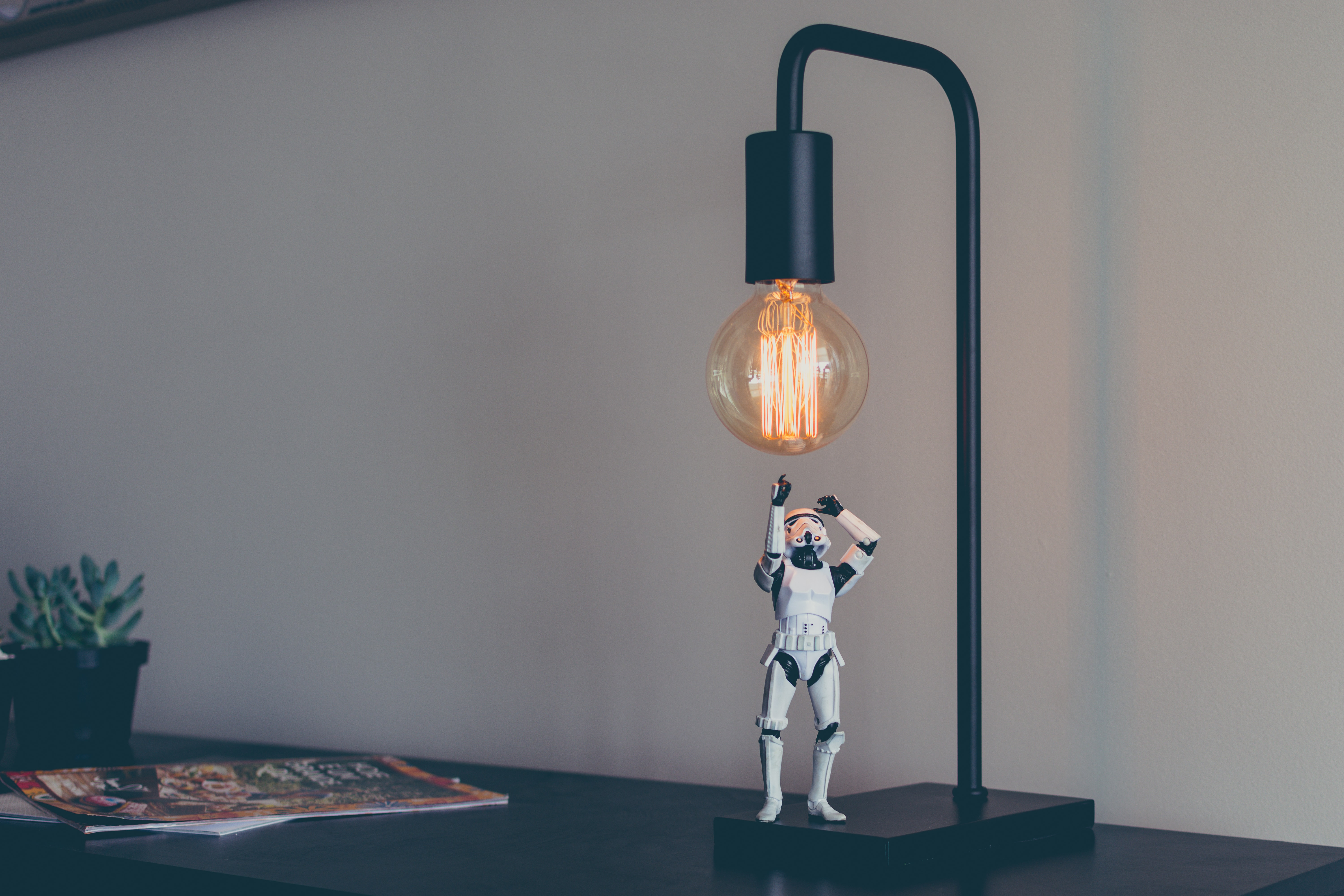 A figurine of a stormtrooper under a desk lamp with an incandescent light bulb
