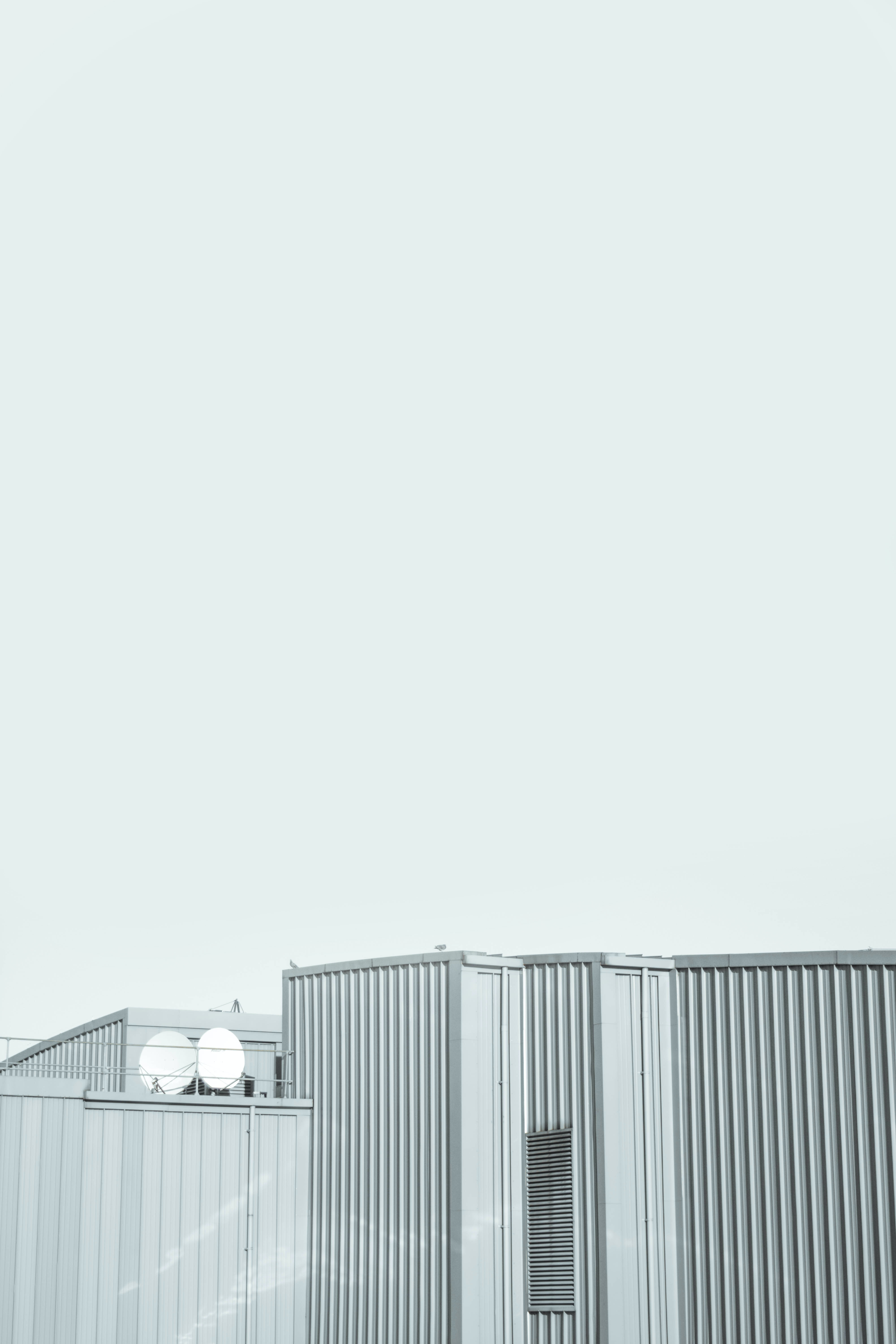 Gray walls of an industrial building under a white sky