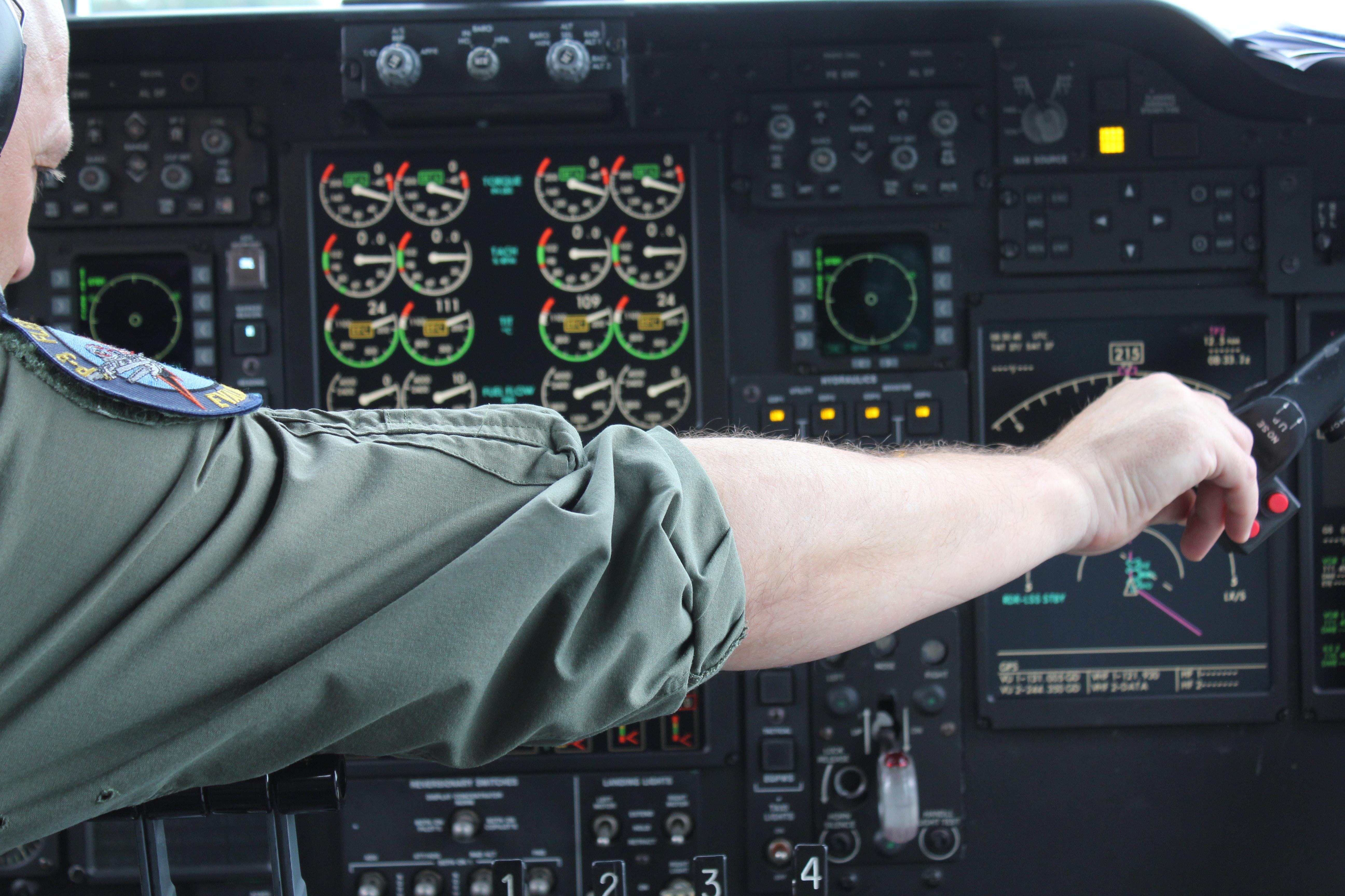 A pilot tuning his cockpit instruments.