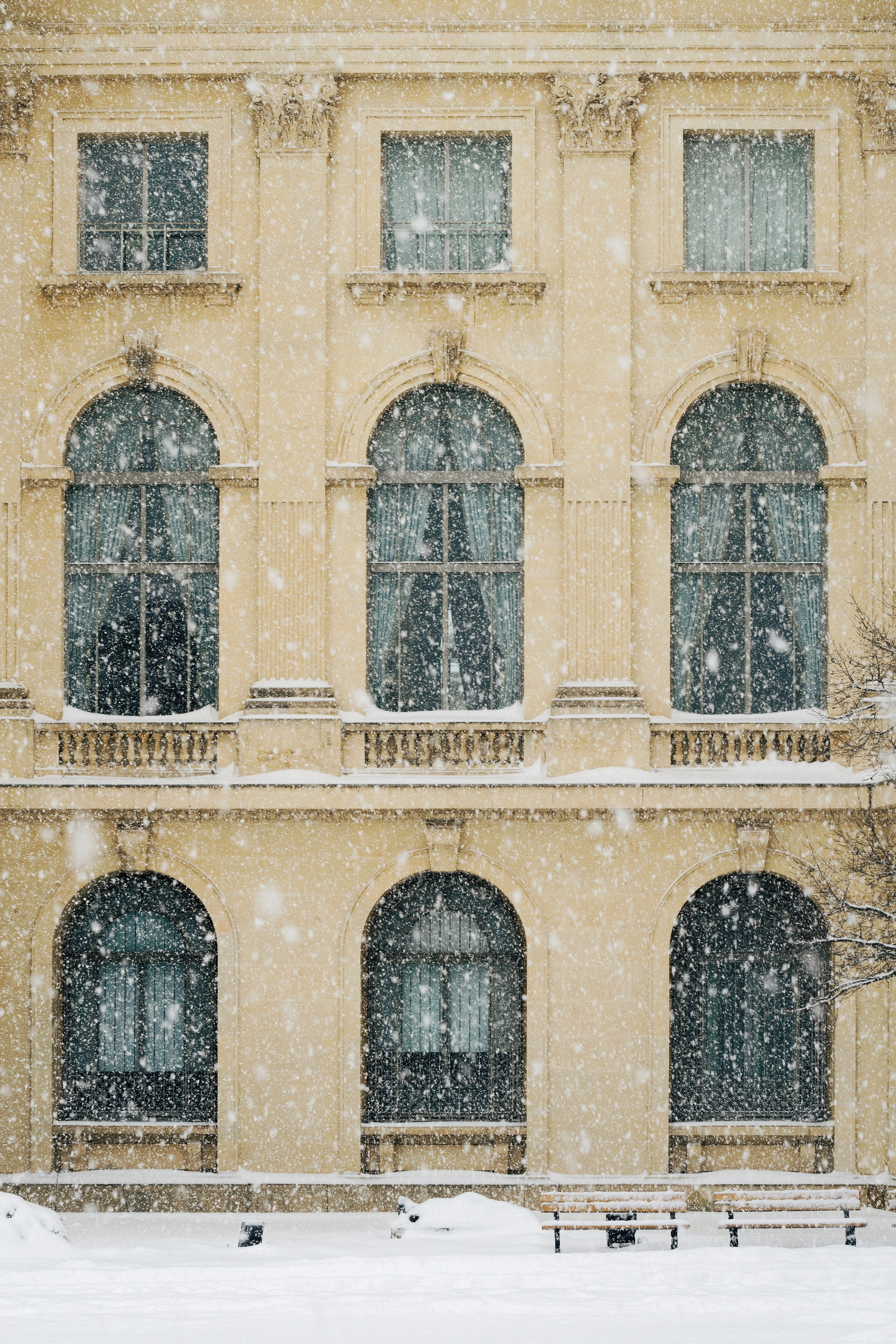 photo of beige concrete 3-storey building with snow