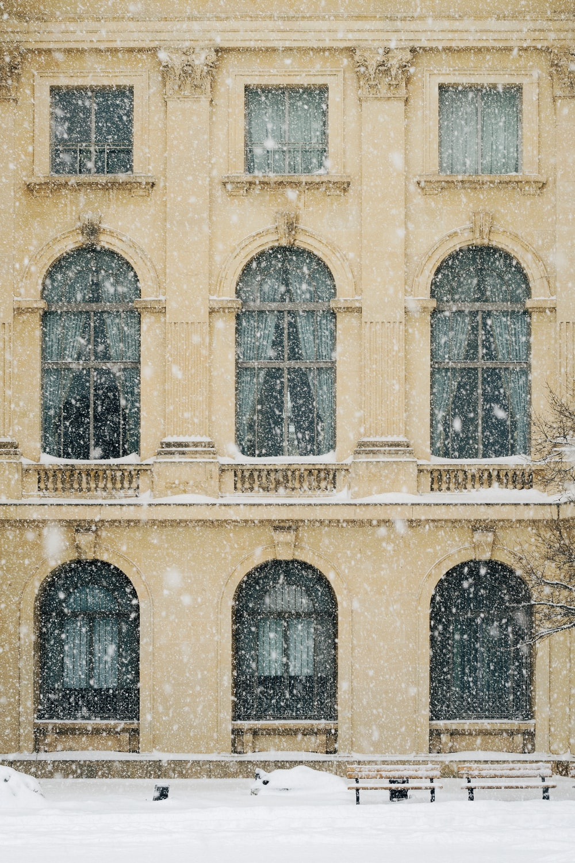 photo of beige concrete 3-storey building with snow