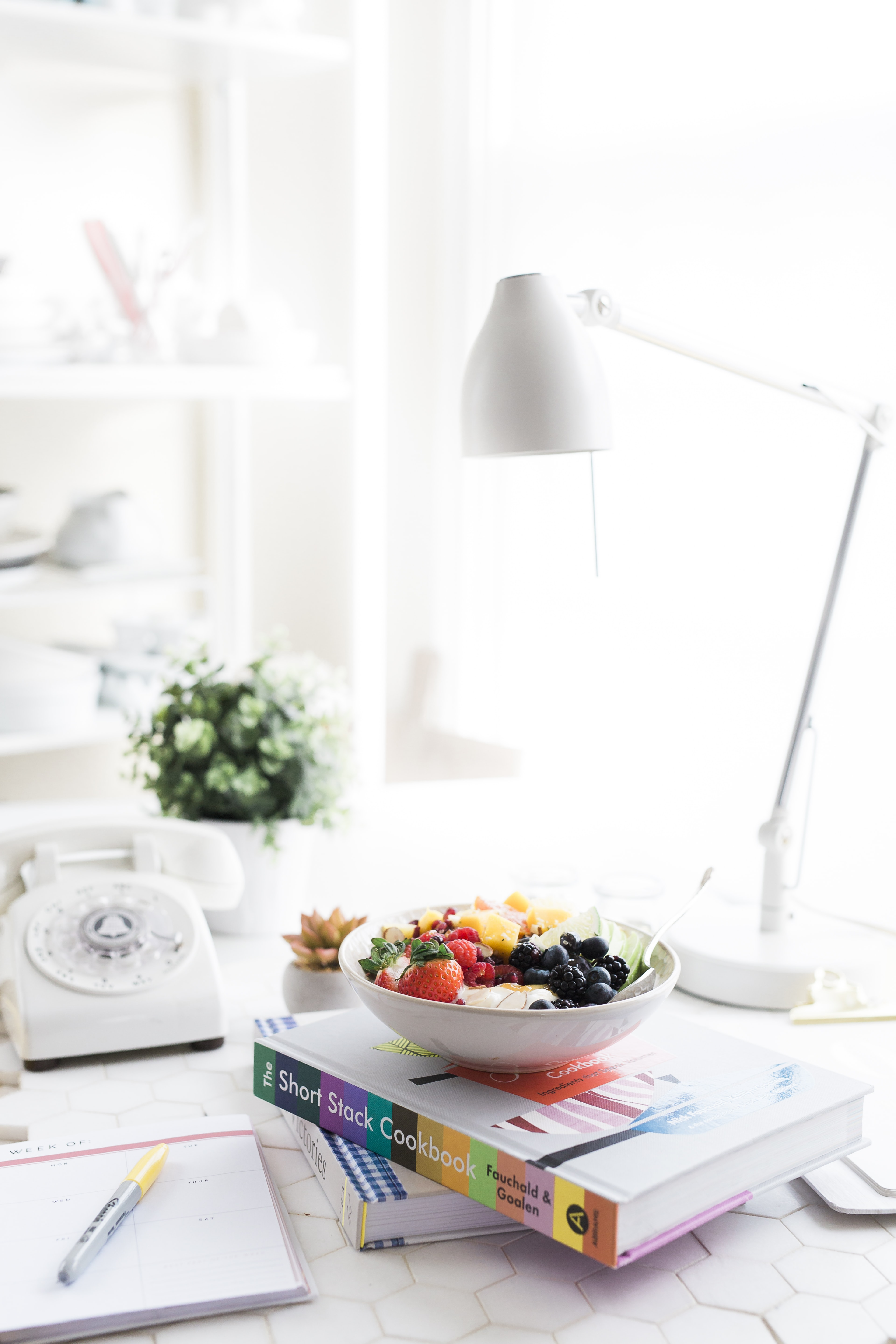 A fruit salad in a bowl on top of a colorful cookbook on a desk