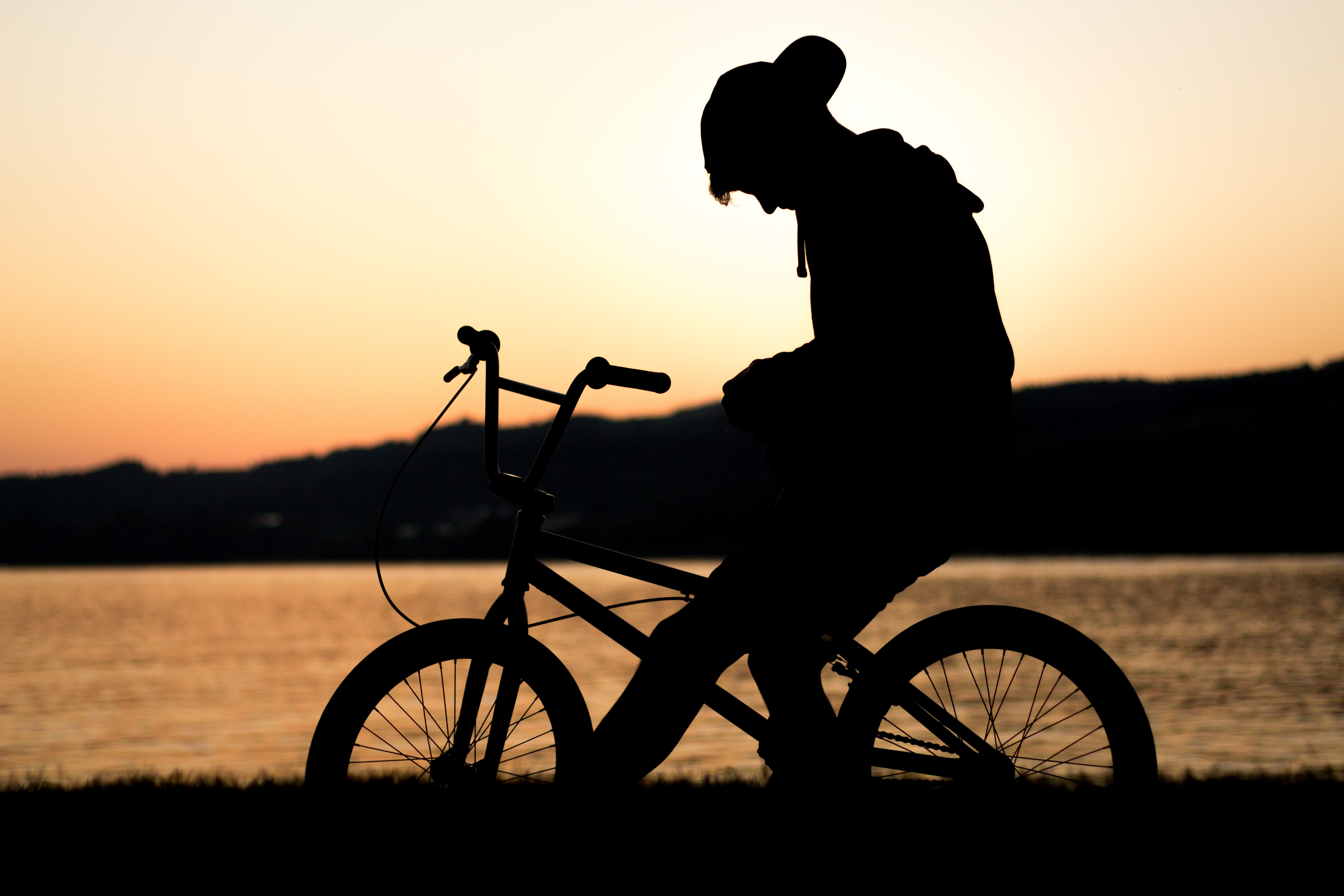 A silhouette of a young person sitting on a bike in front of a lake during a golden sunset