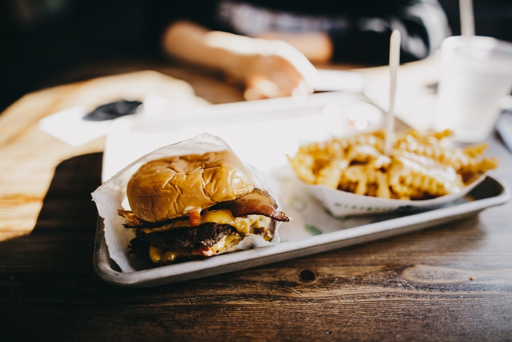 macro photography of burger and fries served on tray