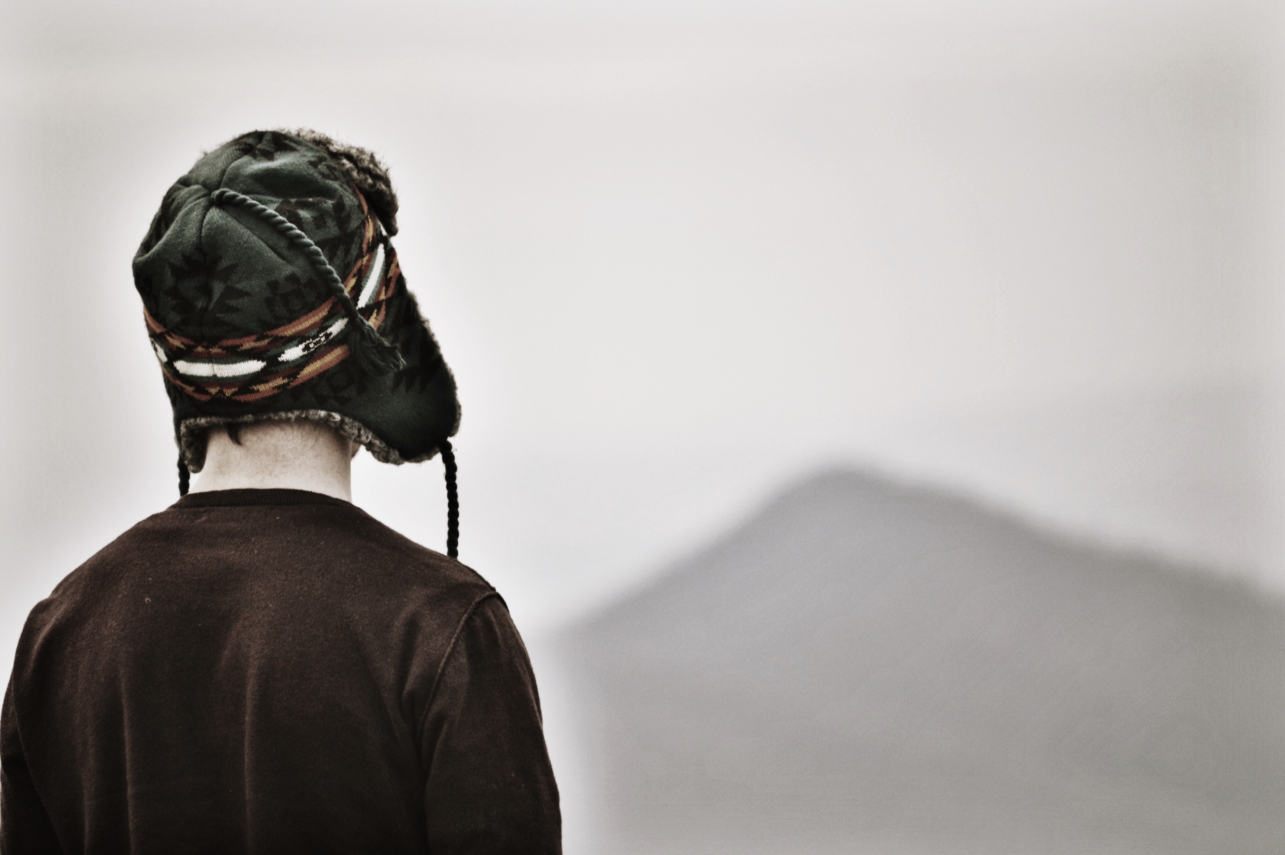 A person in an ear-flap hat looks into the distance in the Blue Ridge mountains