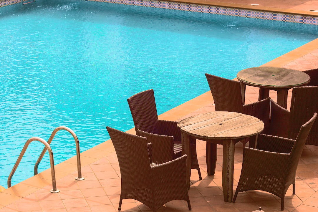 Rattan chairs around small wooden tables by a pool