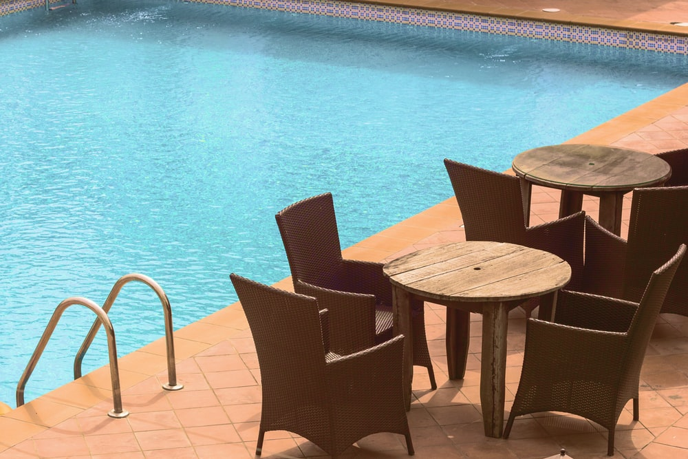 wooden cafe table and chairs beside inground pool