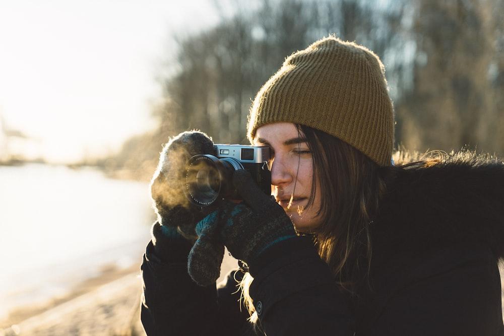 woman holding SLR camera
