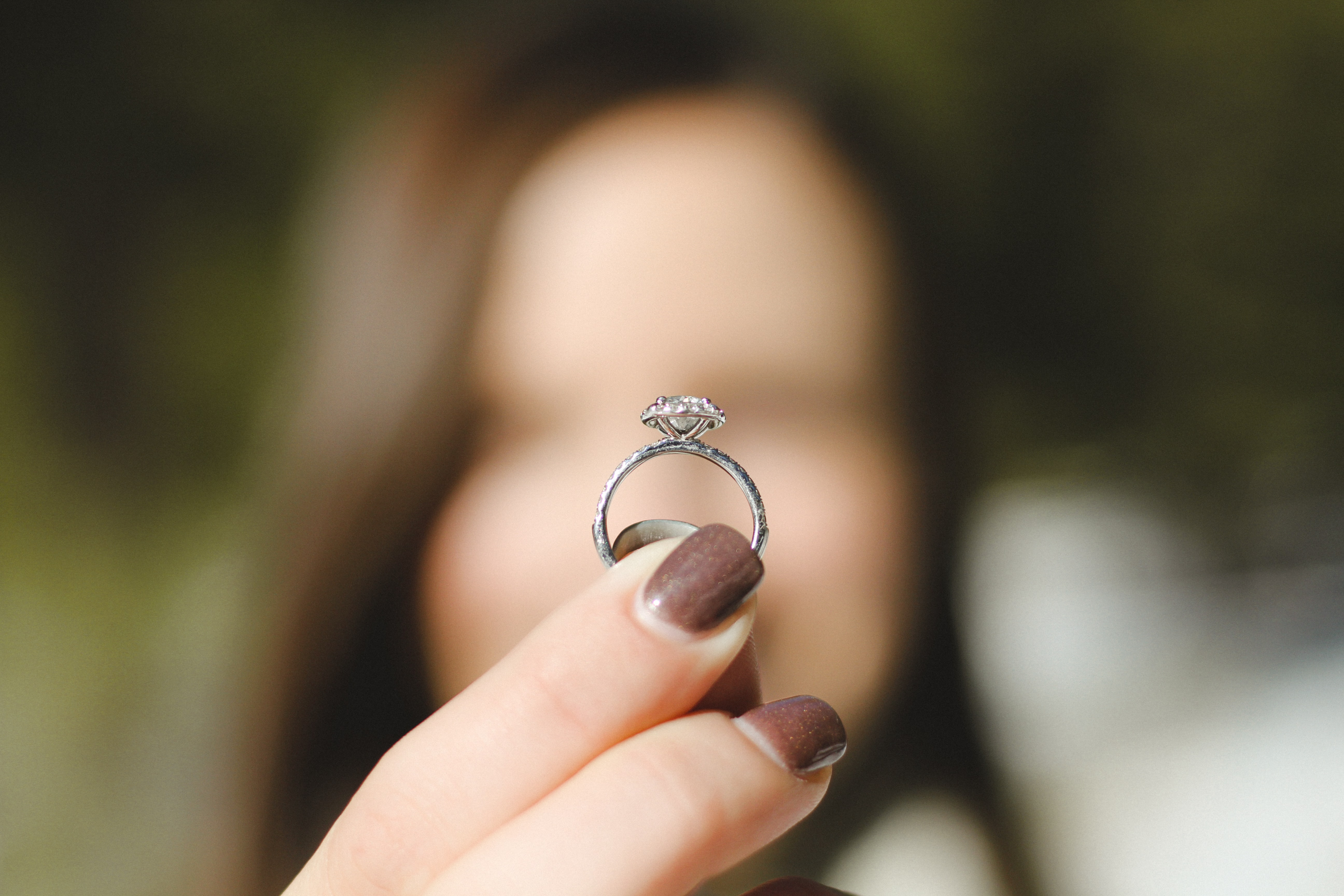 shallow focus photography of woman holding a diamond ring