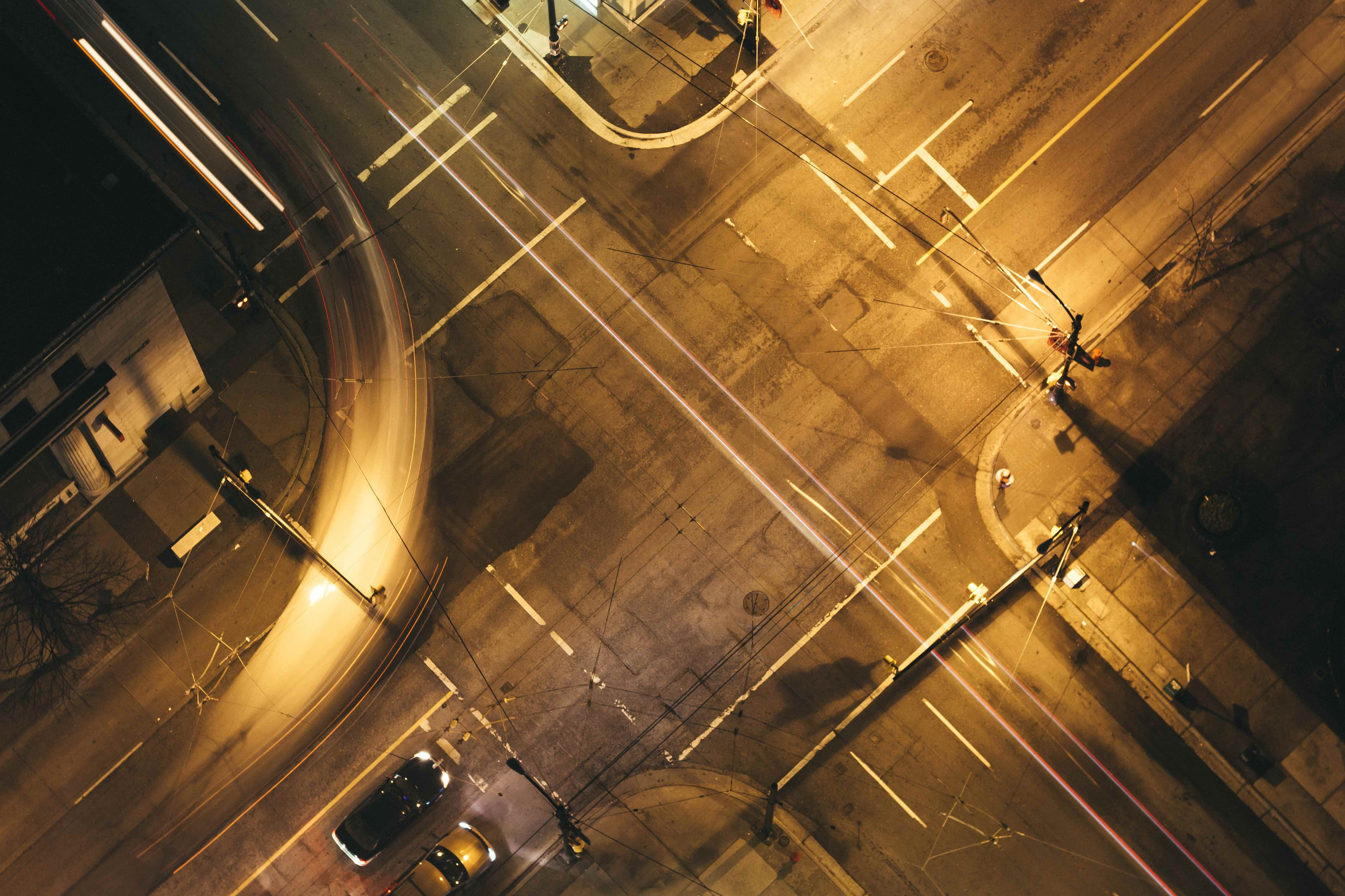 Drone aerial view of worn down asphalt intersection with car light trails and cars at night in Vancouver Lookout