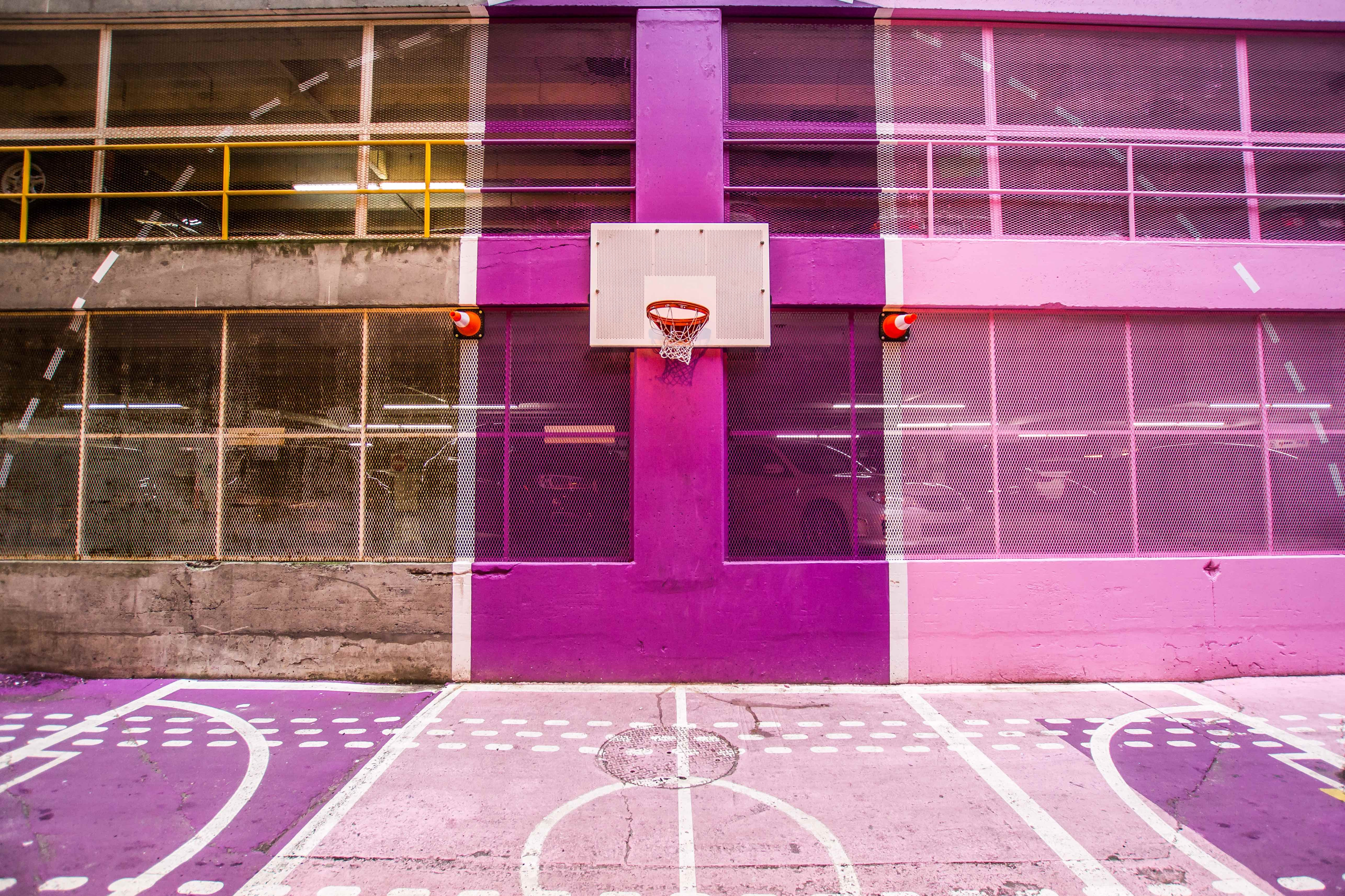 A colorful pink and purple outdoor basketball court