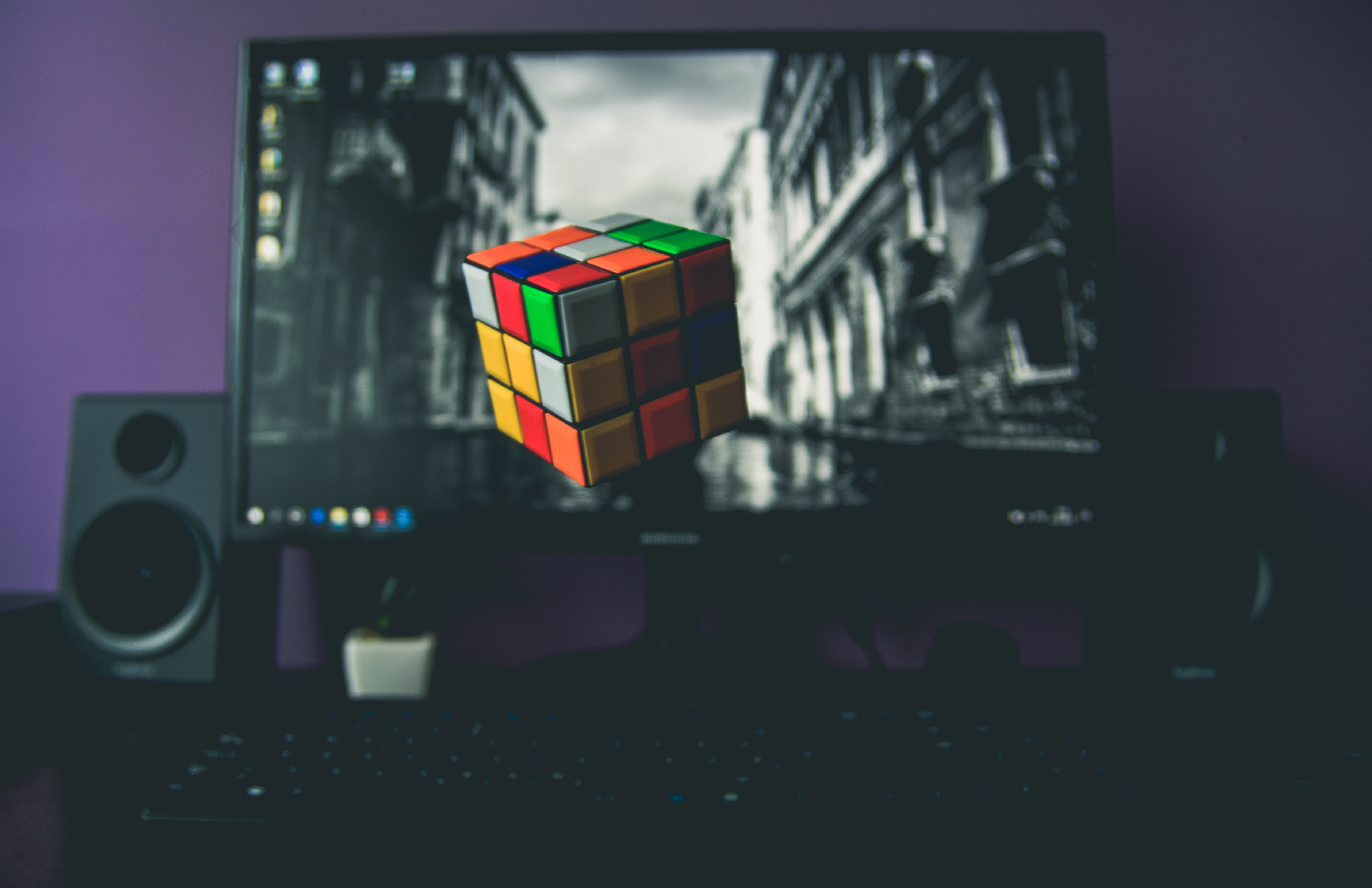 Colorful rubik's cube floats in front of computer monitor and speakers
