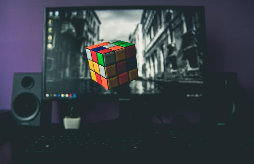 turned on flat screen computer monitor displaying 3x3 Rubik's cube