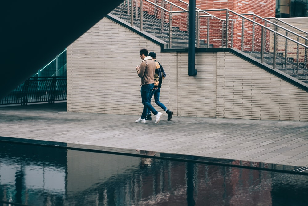 two man walking beside stair and body of water at daytime