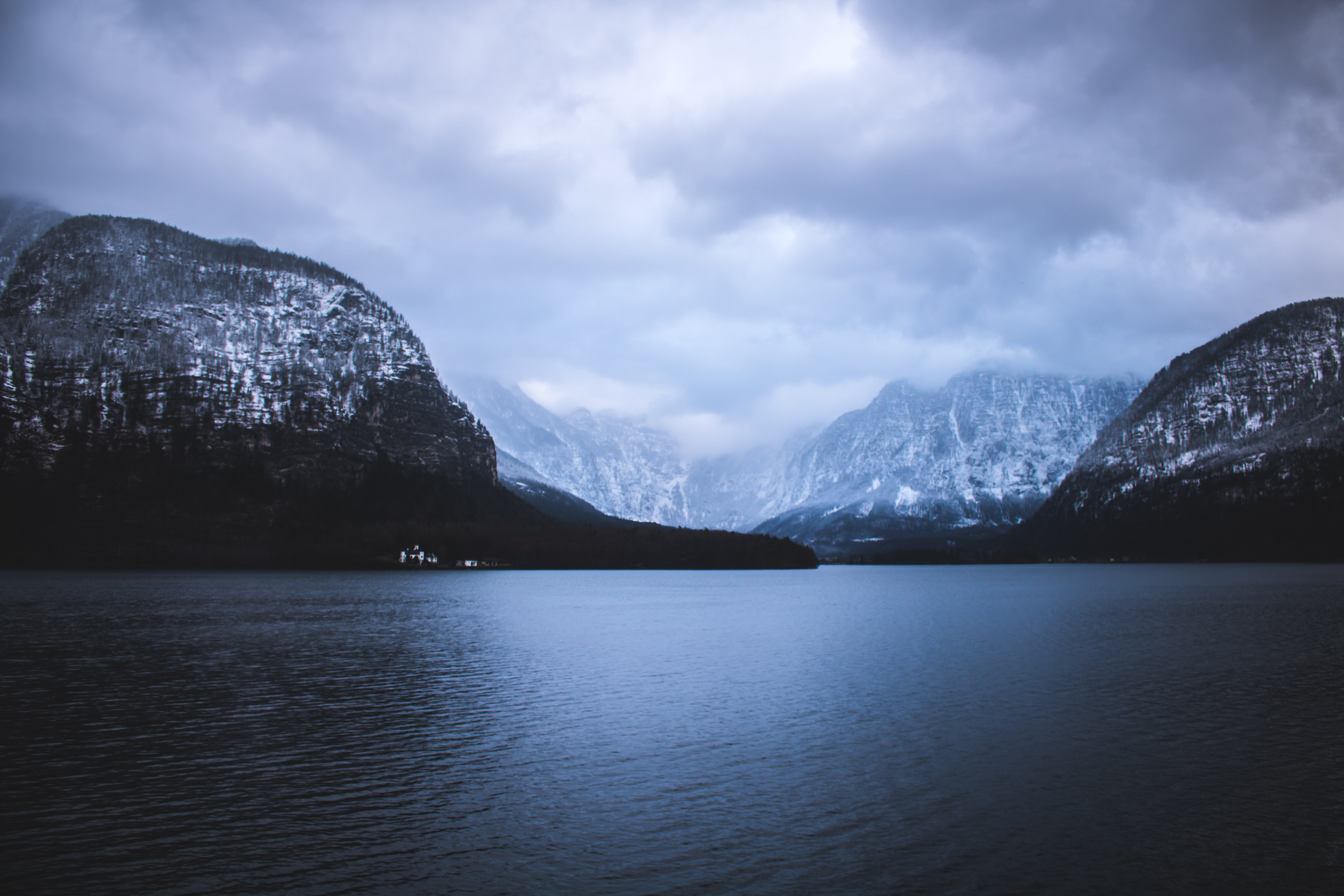 landscape photography of mountains near body of water under cloudy sky