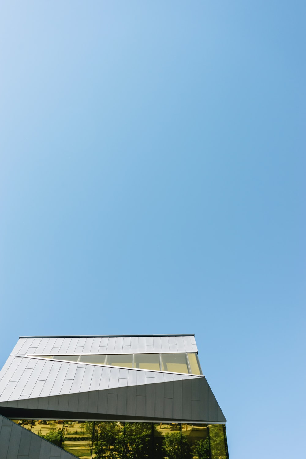 low-angle photography of white concrete building under clear blue sky