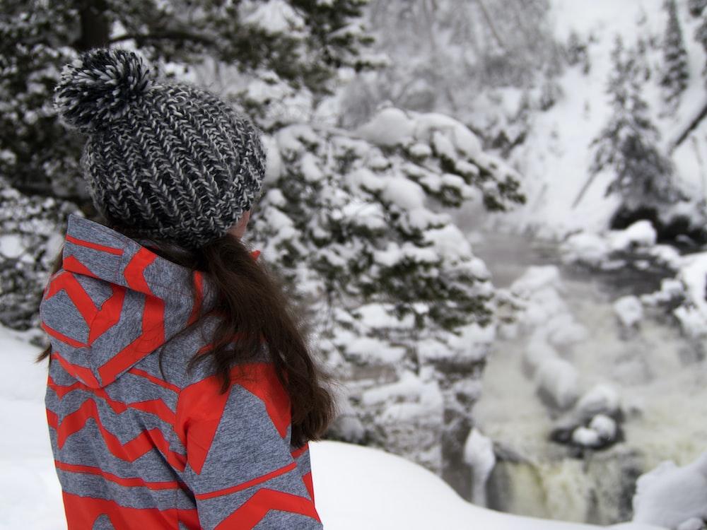 woman standing on snow field near trees