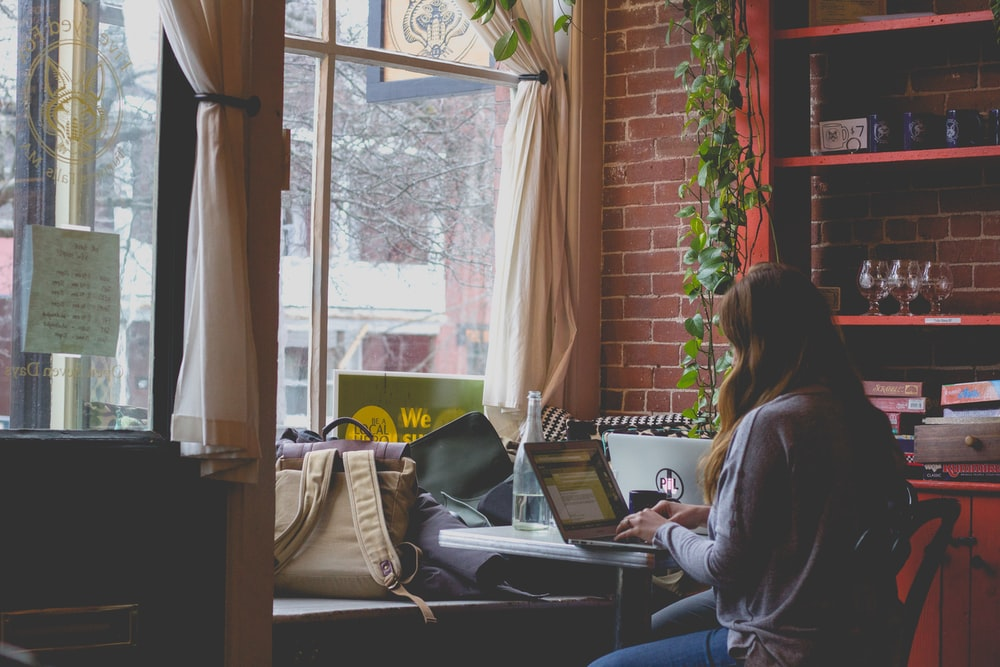 woman using computer sitting on black chair