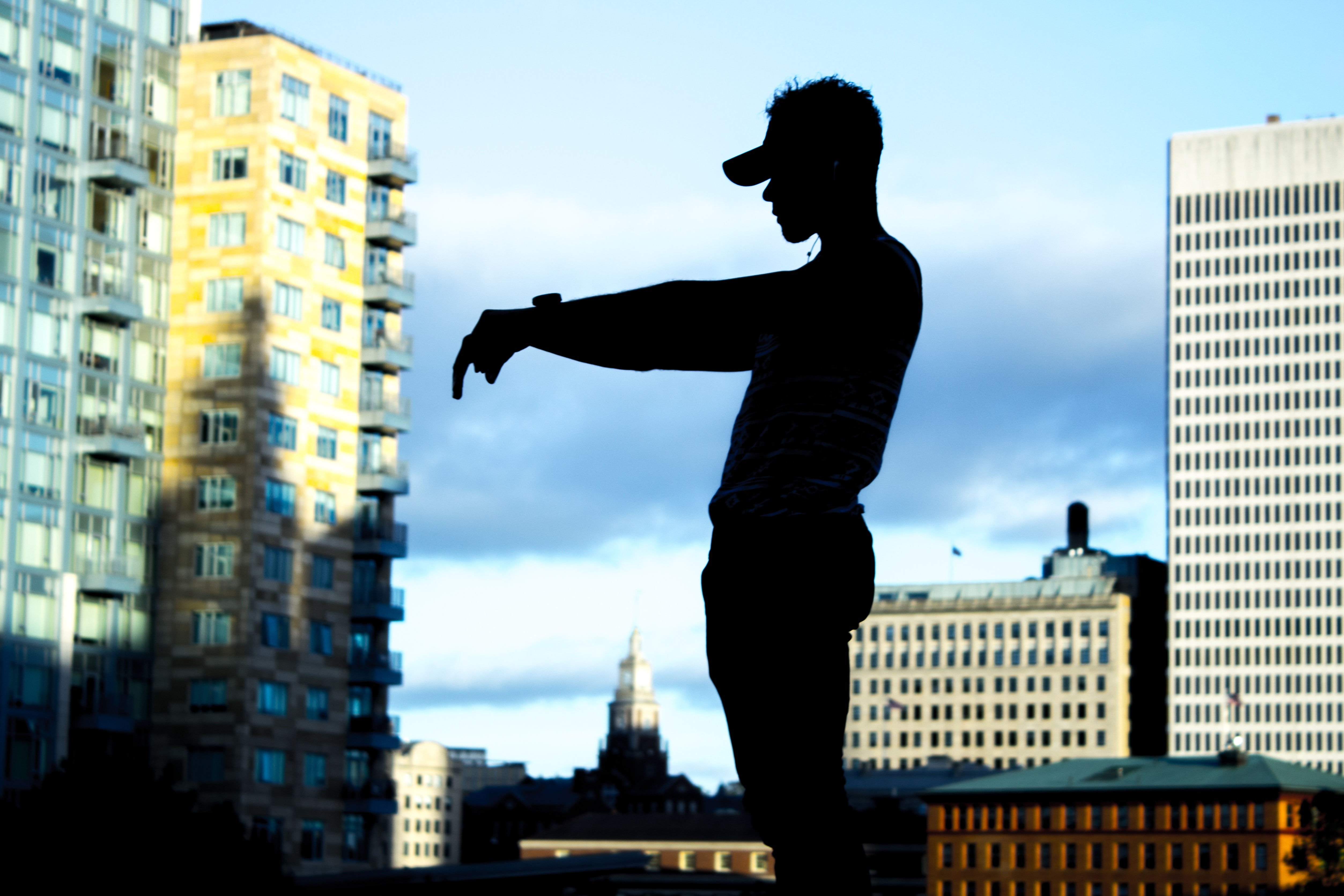 silhouette of man standing in front of high-rise buildings