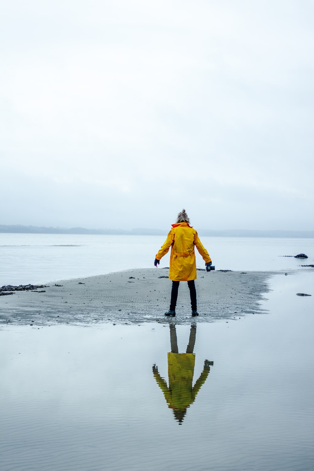 person in yellow coat on gray sand surrounded by water