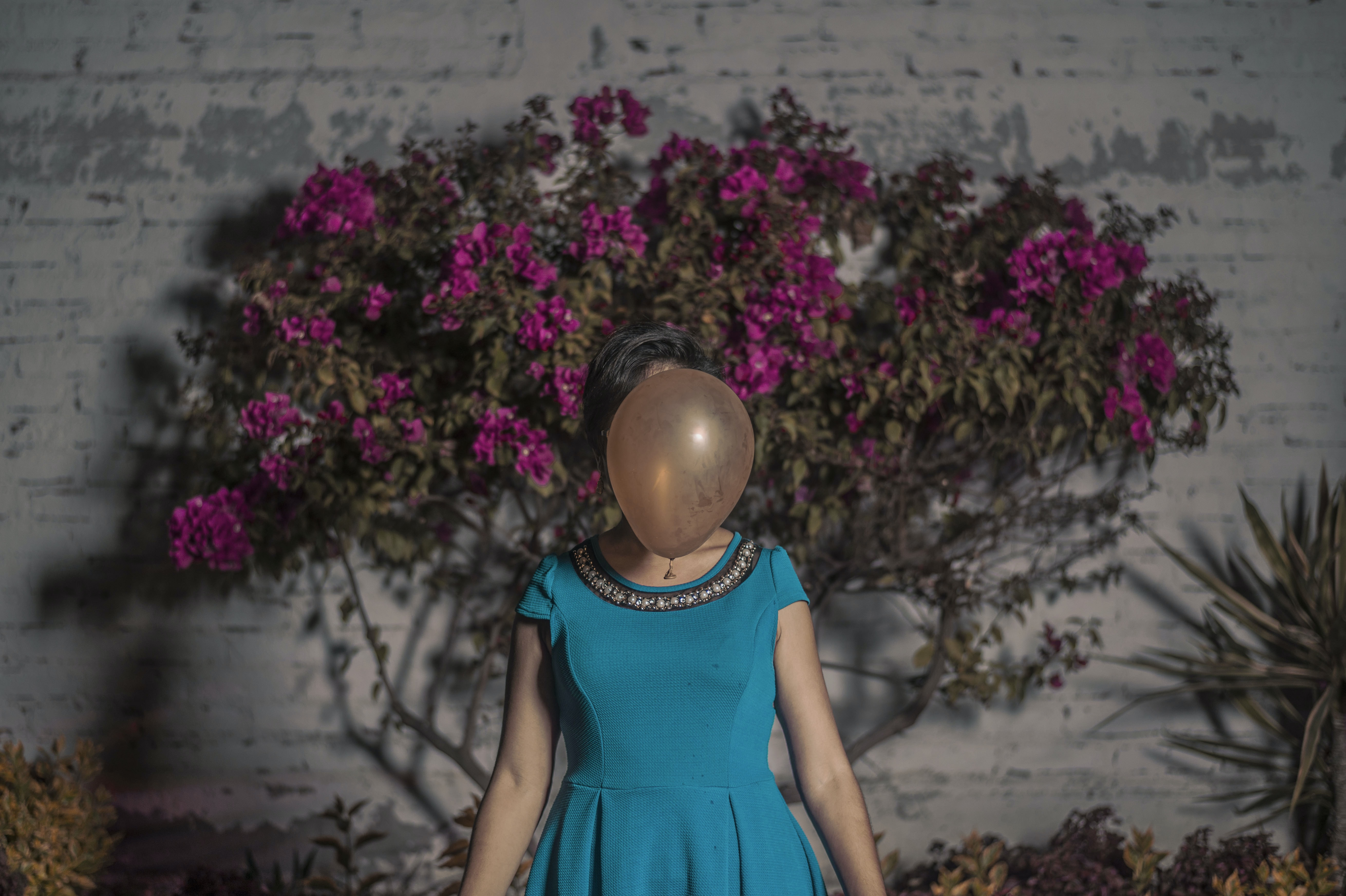 woman standing in front of brown balloon