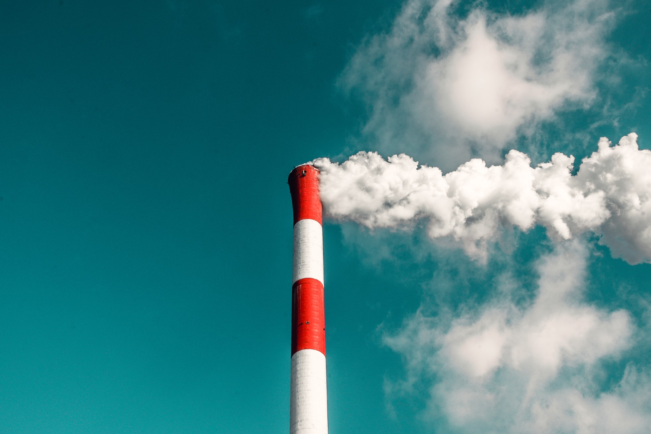 Photograph of a smoke stack with white smoke billowing out.
