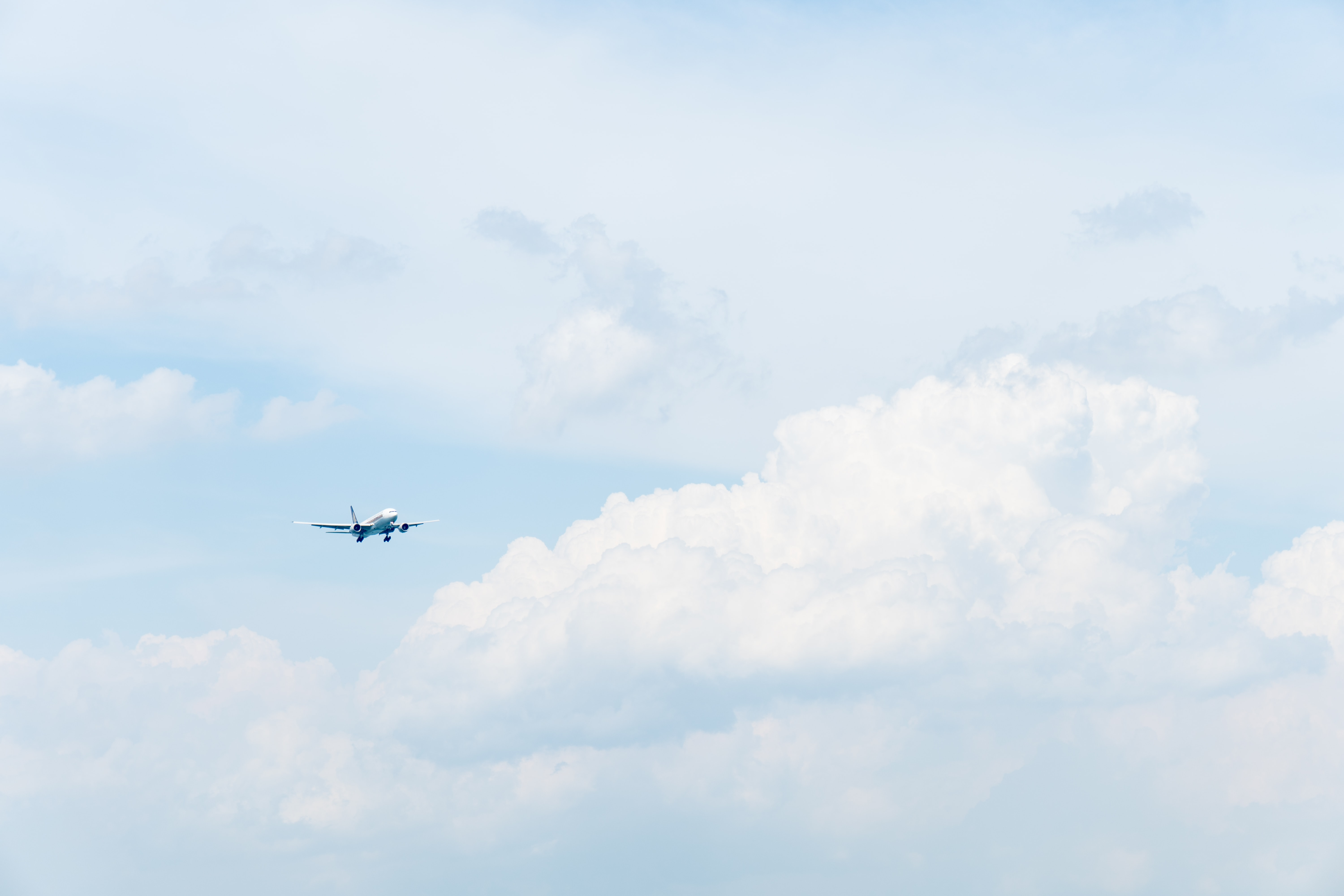 photo of white commercial airplane flying in sky under white clouds