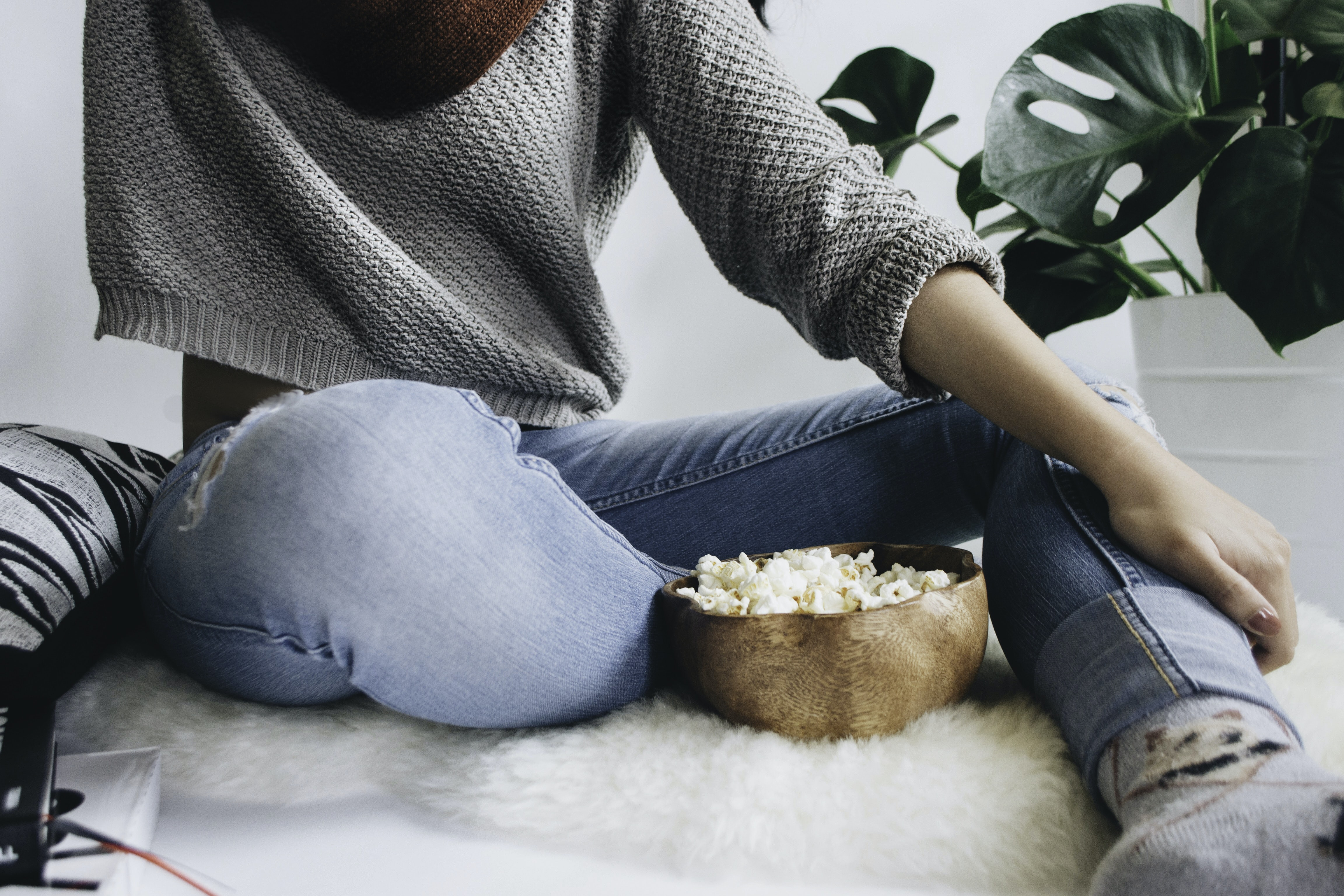 Woman in a cropped gray sweater sits on a furry rug with a bowl of popcorn