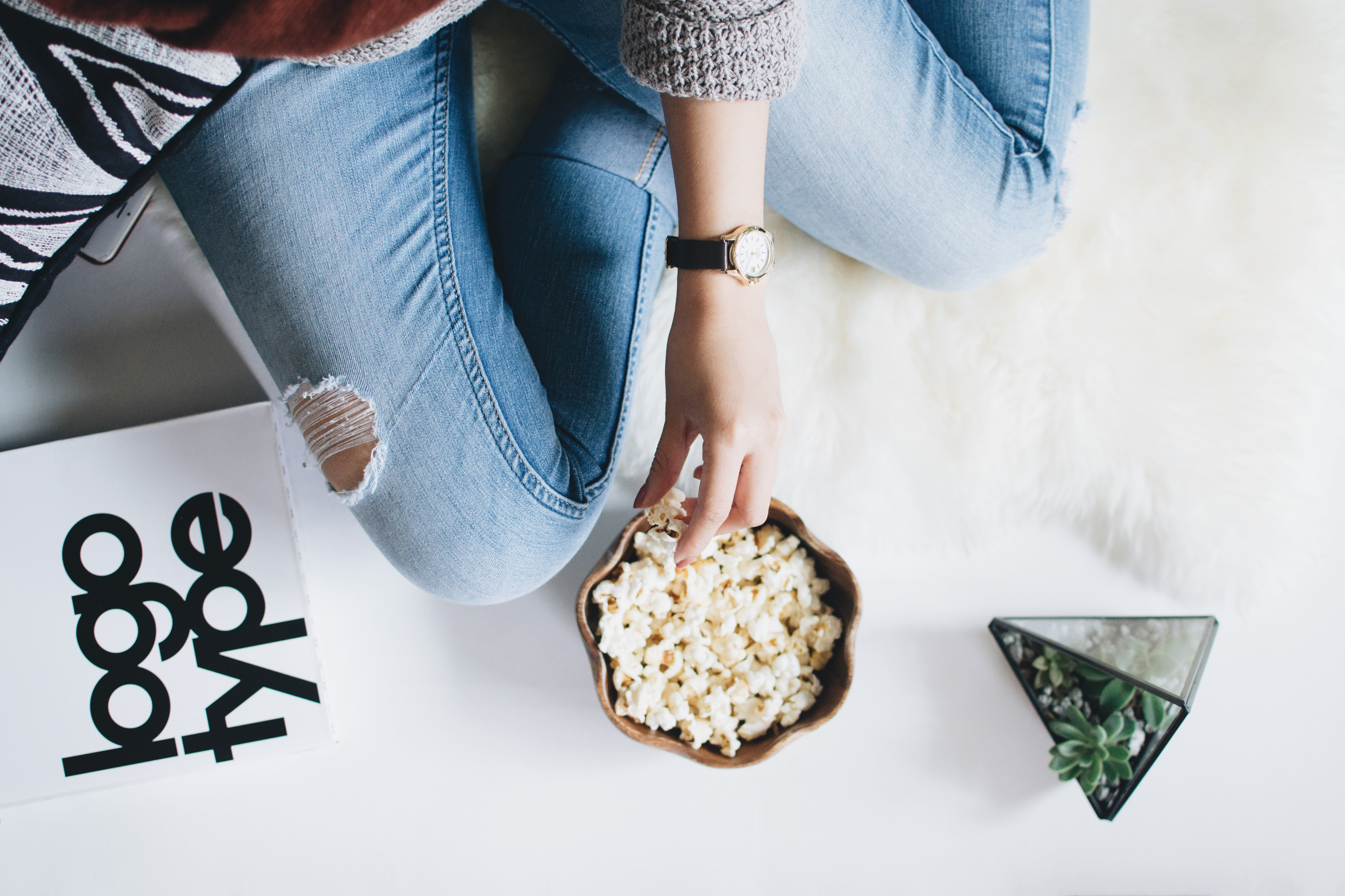 A person in ripped jeans eating popcorn alongside a succulent plant and typographic sample