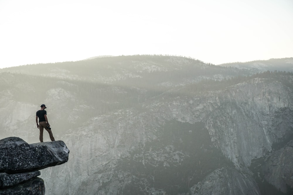 person standing near rock cliff