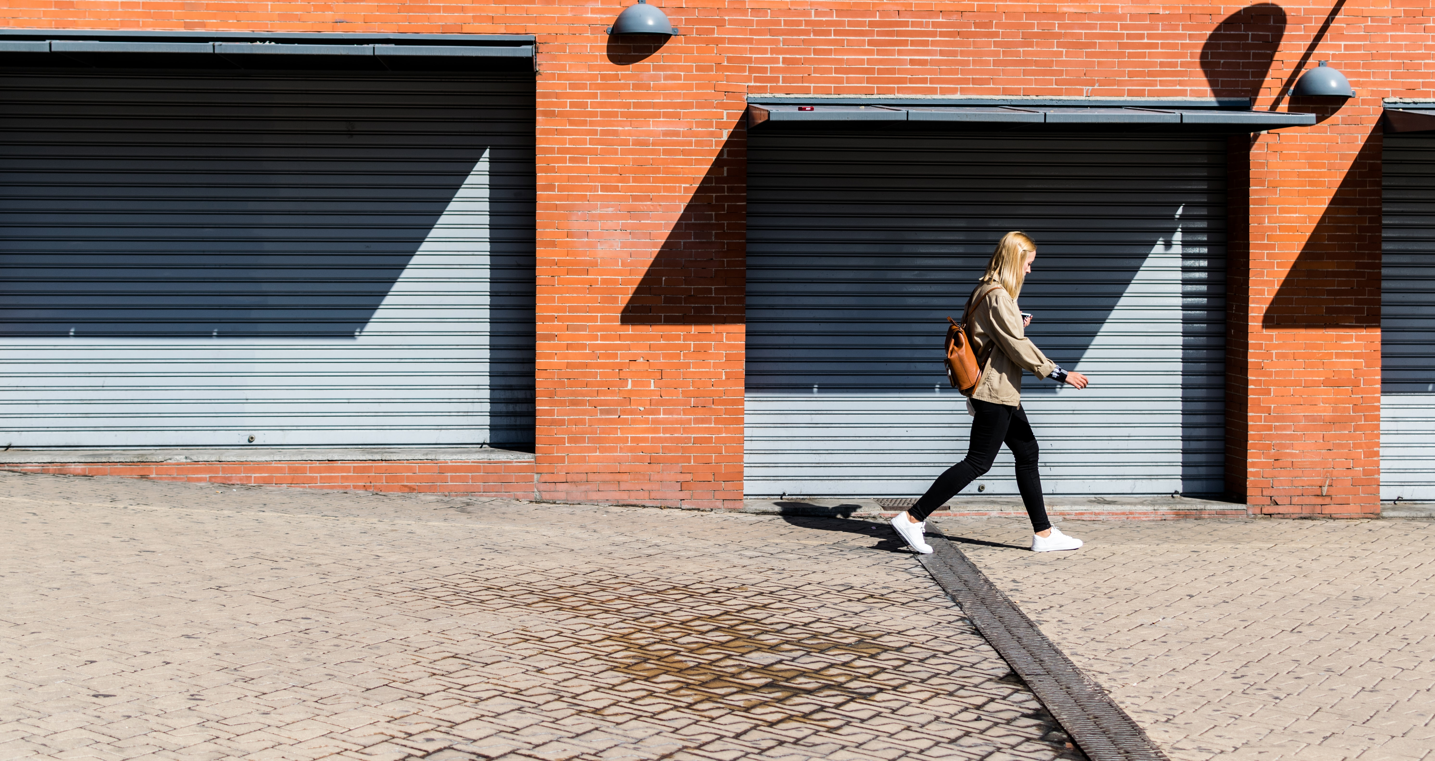 A woman is walking past a brick building at the Madrid Atocha Railway Station.