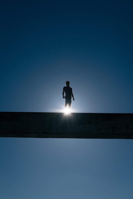 silhouette of man standing on bridge