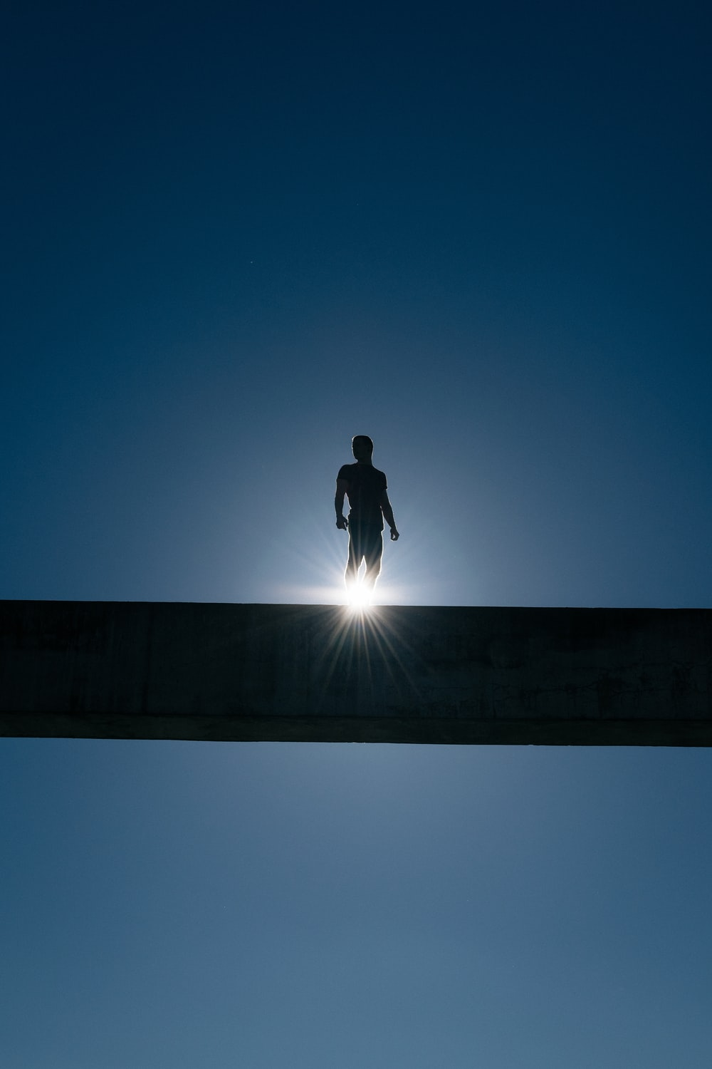 silhouette of man standing on bridge