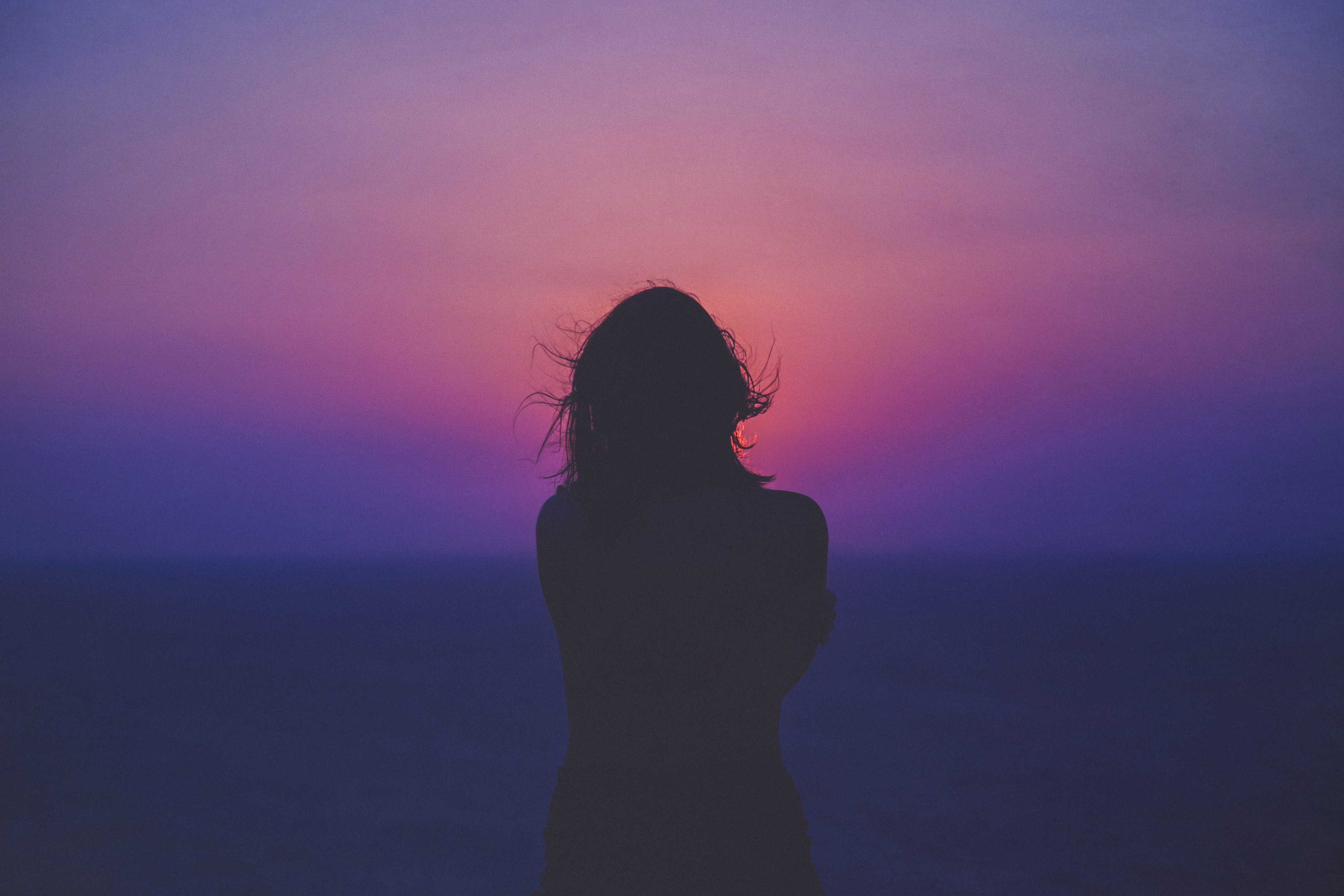 Silhouette of a woman against a pink and purple sunset, hair floating in the wind