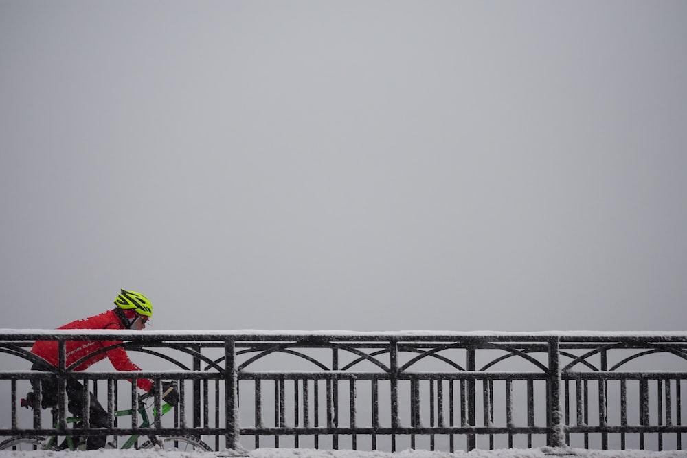 man in red jacket riding bike on bridge