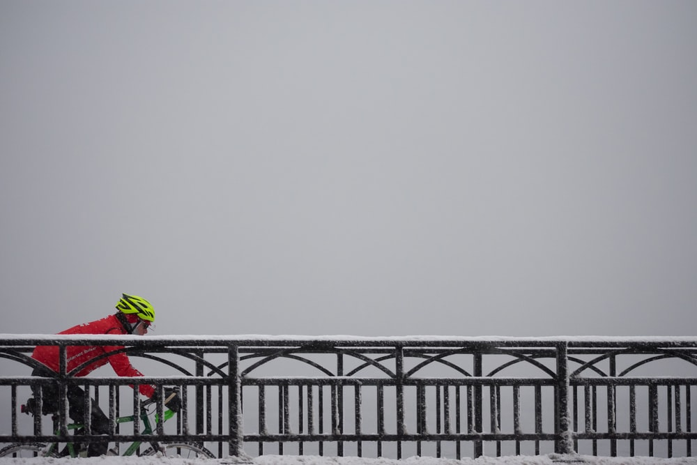 man in red jacket riding bike on bridge