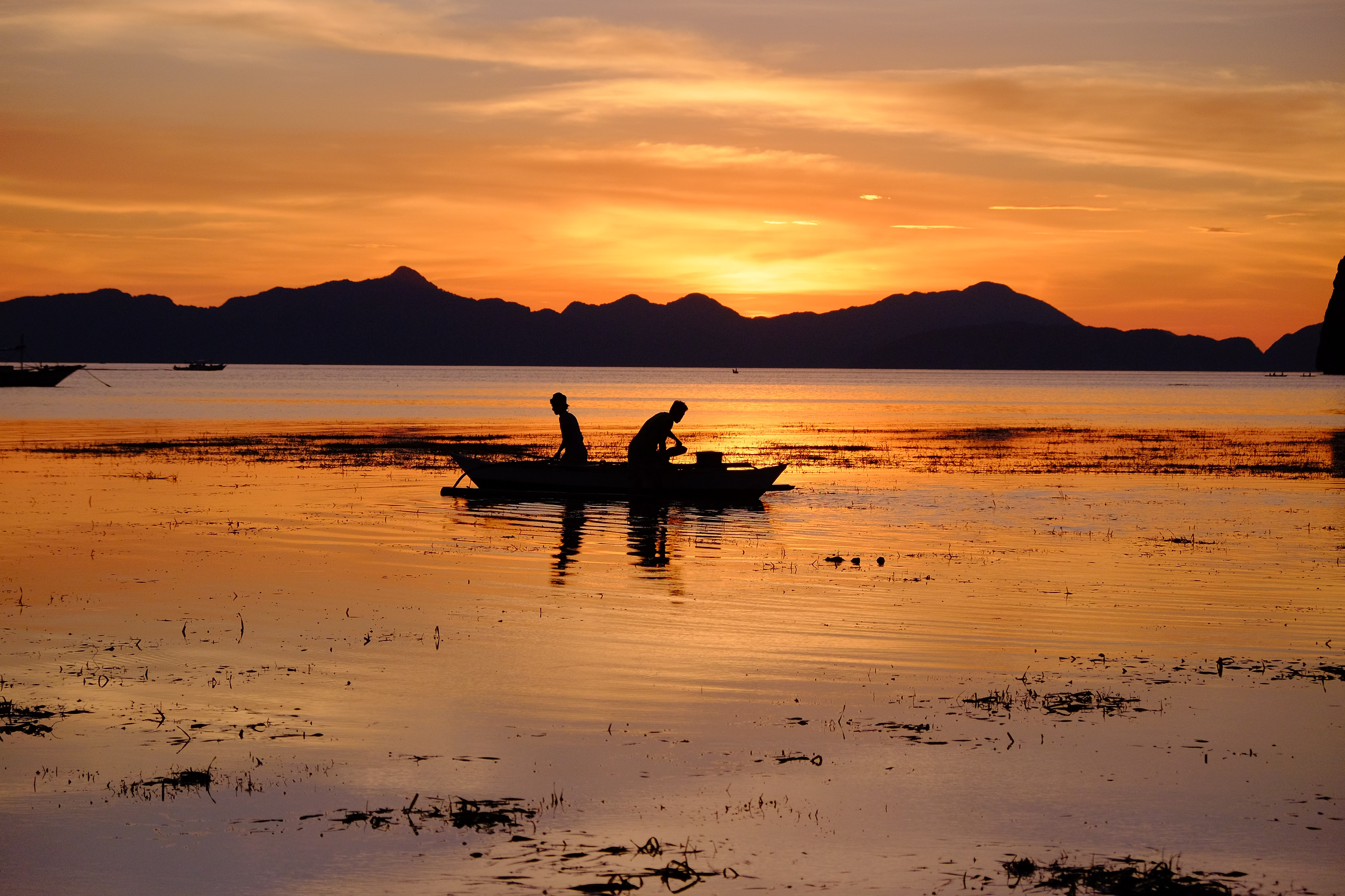 Two fisherman in a boat, their reflection on the water, silhouetted against sun and orange sky