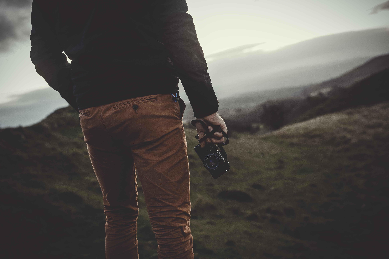 man standing uphill holding black digital camera