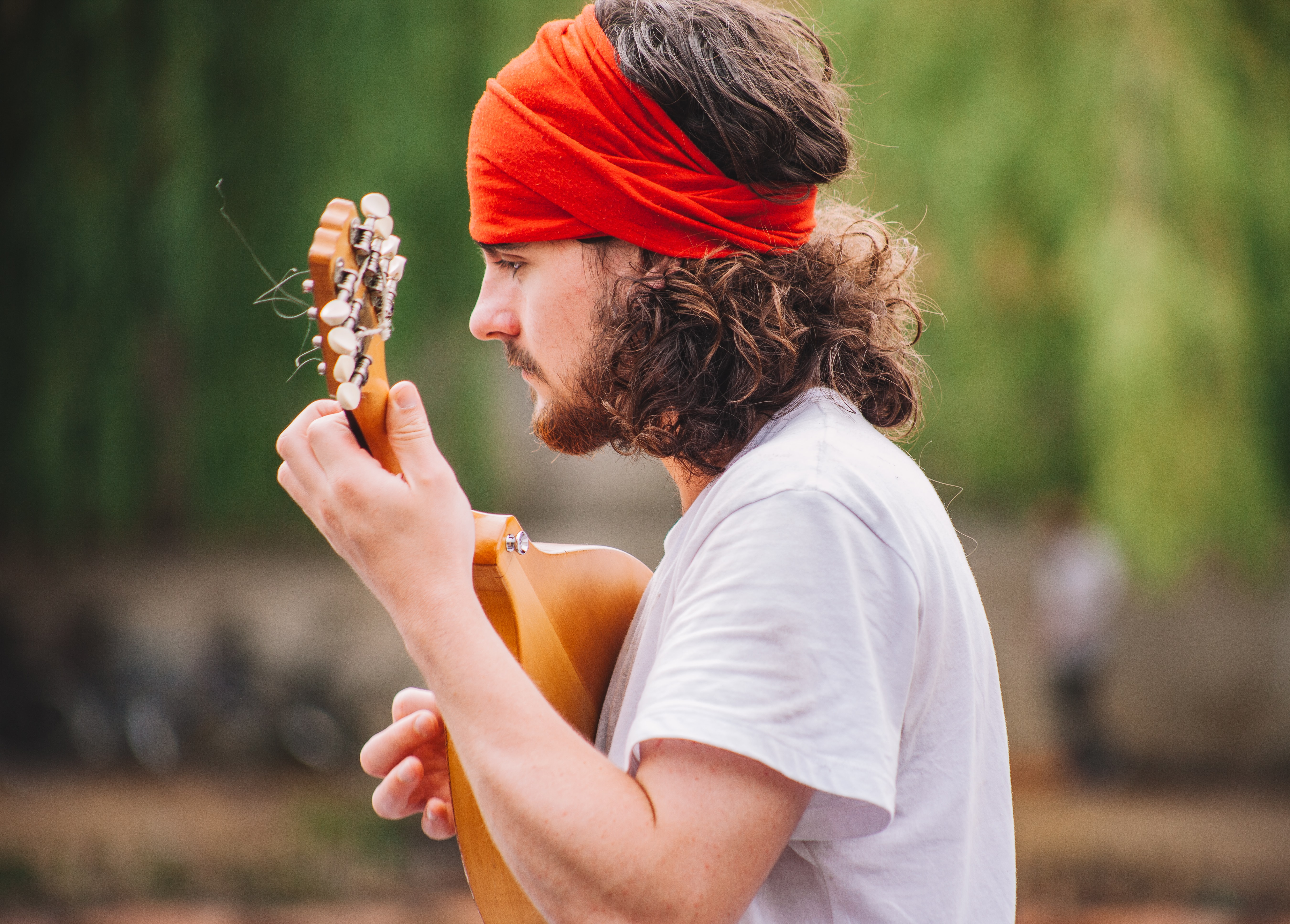A bearded man in a red hairband and a white t-shirt playing the mandolin