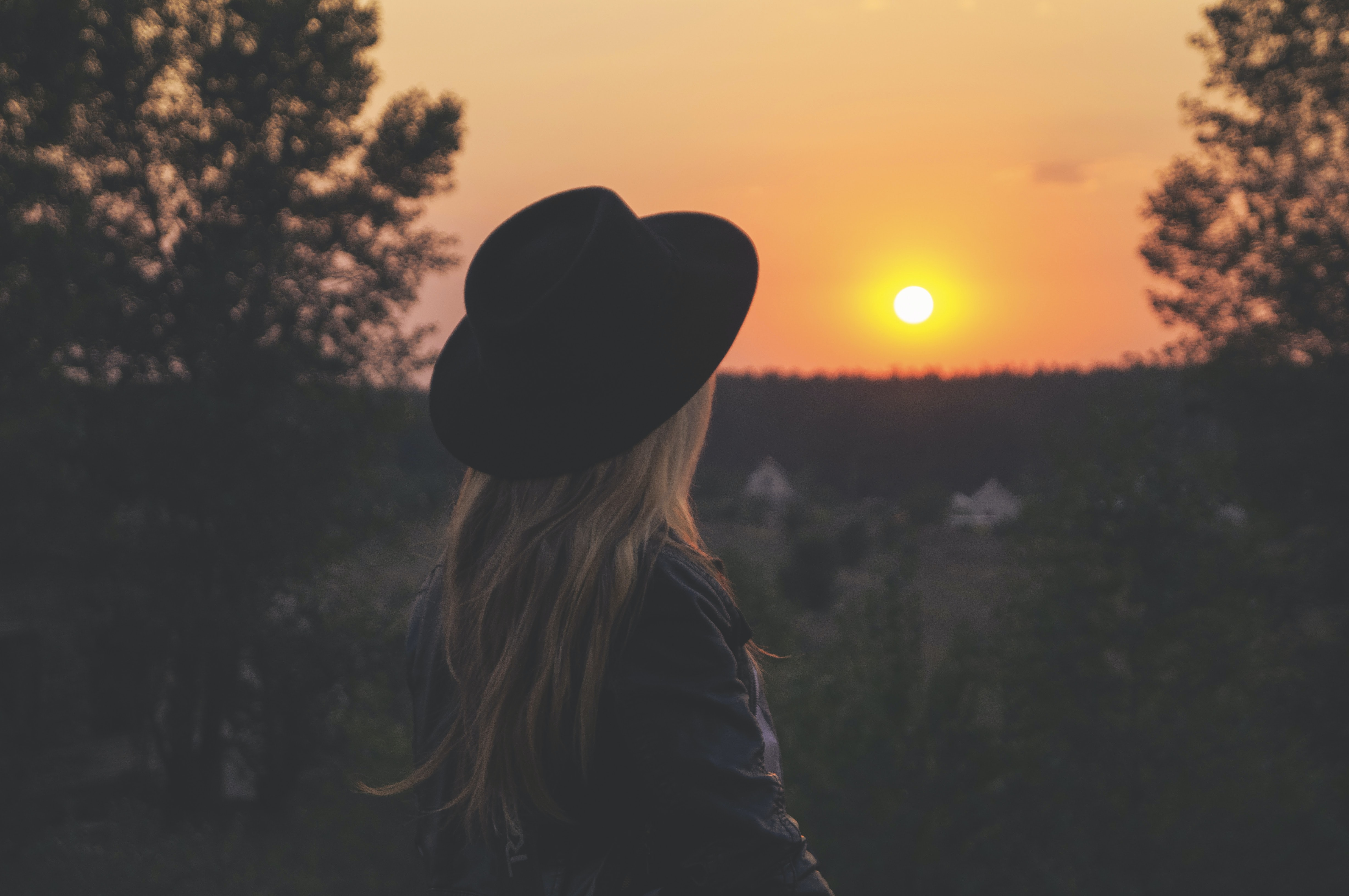 woman wearing black hat staring at sunset