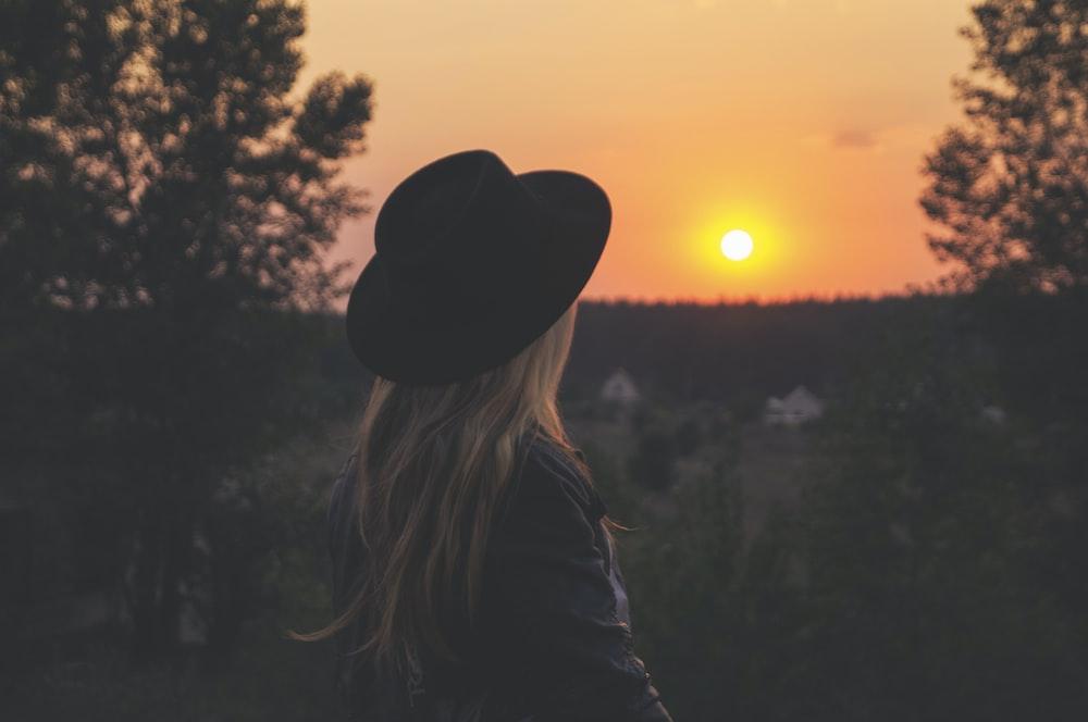 woman wearing black hat staring at sunset